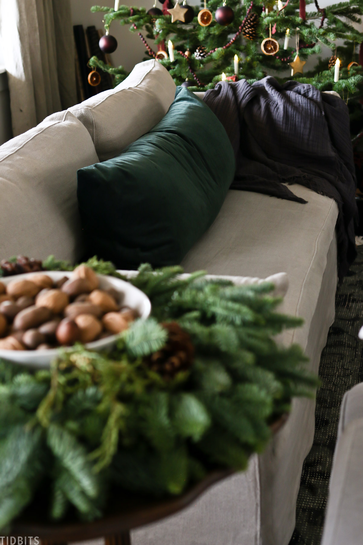 centerpiece that looks like a wreath is placed on side table next to couch