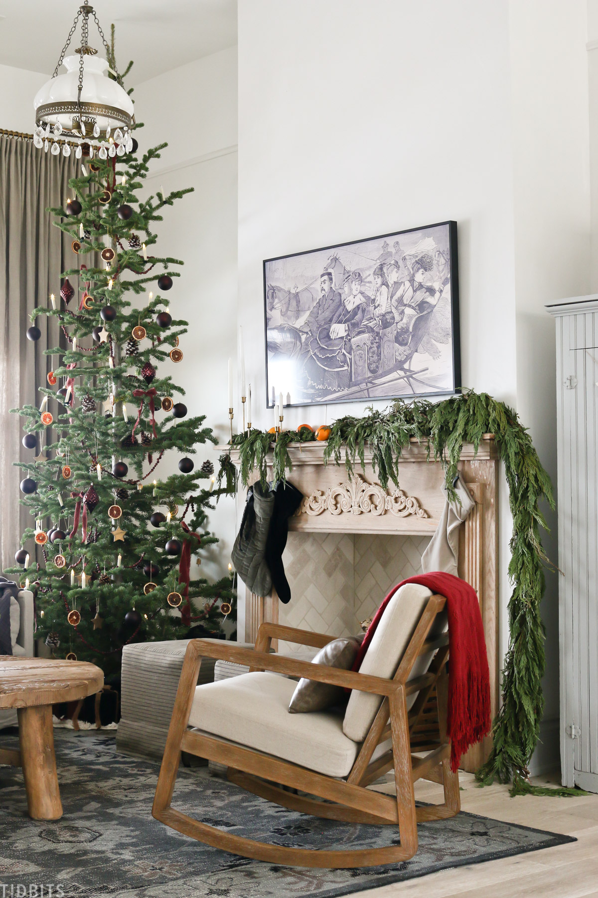 living room with European Old World Christmas decorations with arm chair, coffee table, and mantel with TV mounted to the wall