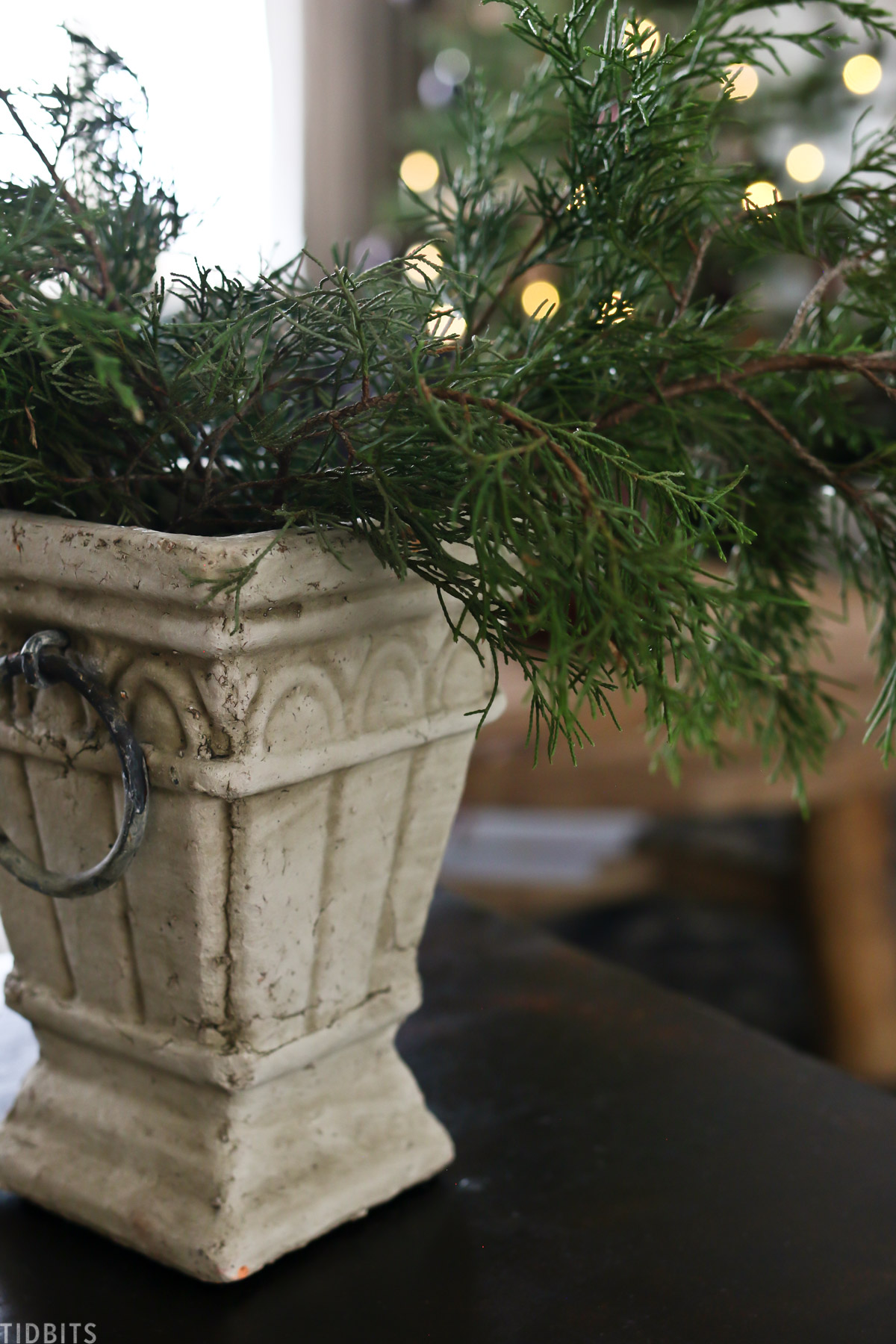 centerpiece vase with tree branches hanging out of it resembling a Christmas tree