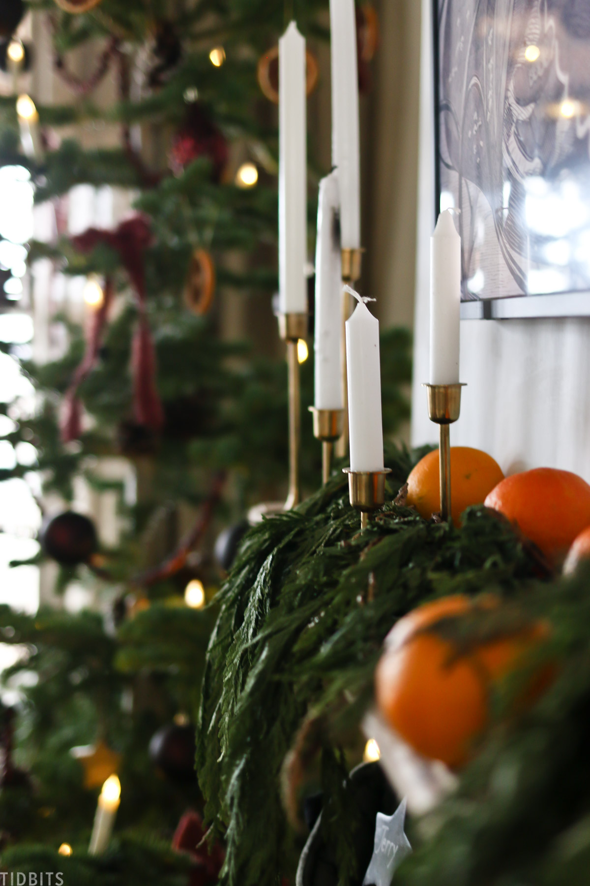 candles and oranges hanging on top of a living room mantel