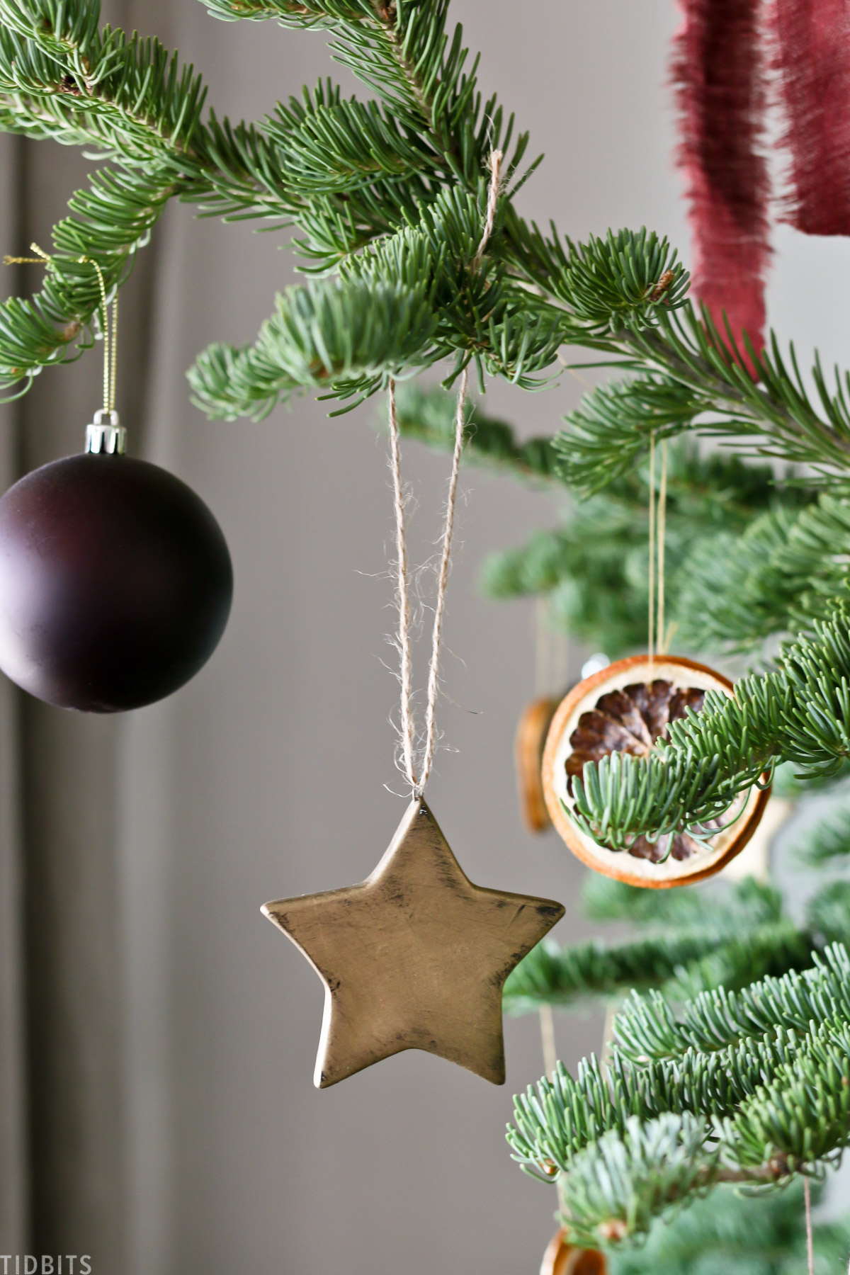 ceramic star hanging off Christmas tree branch next to round ornament and orange garland