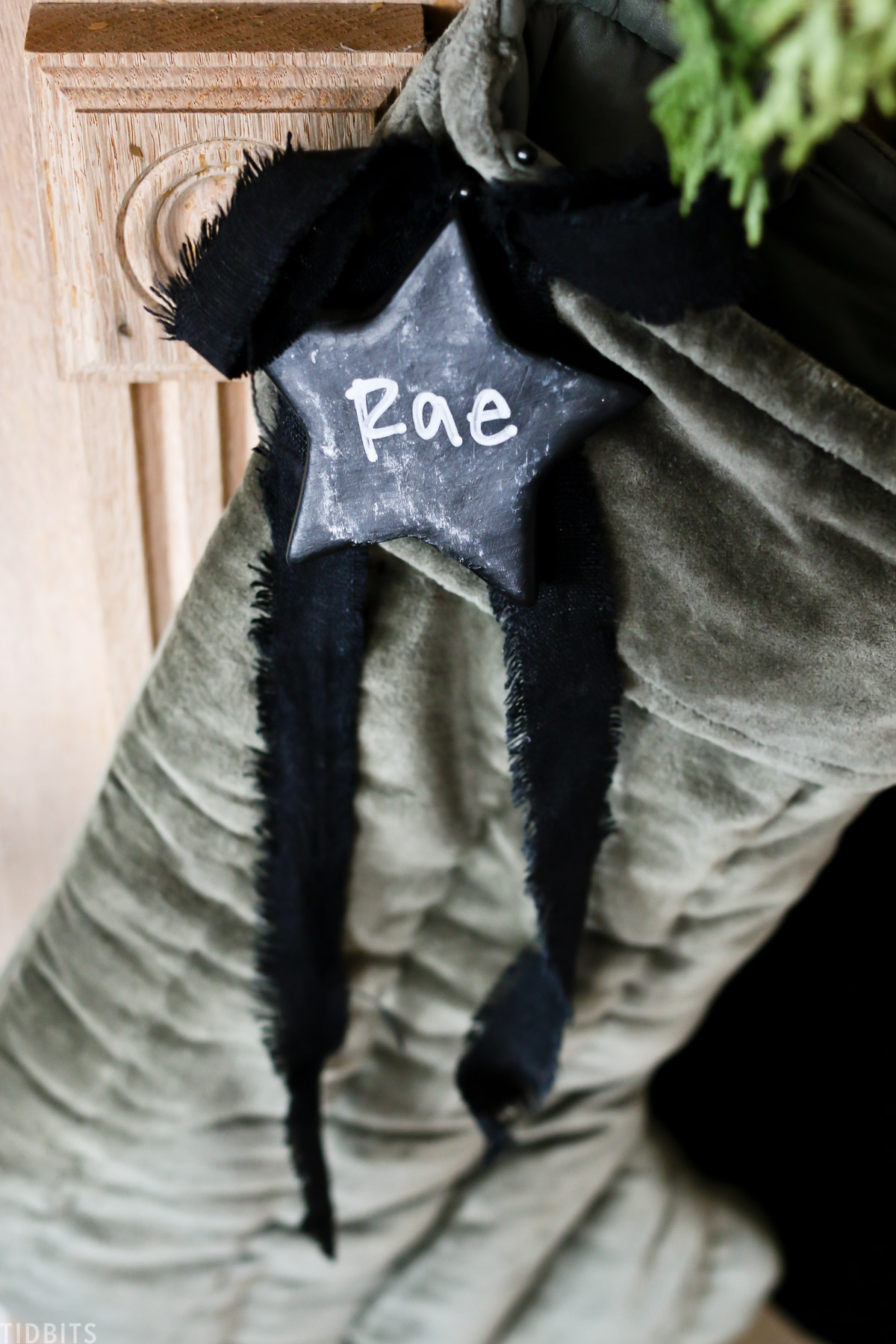 ceramic star with the name Rae written on it that's hanging off green stocking