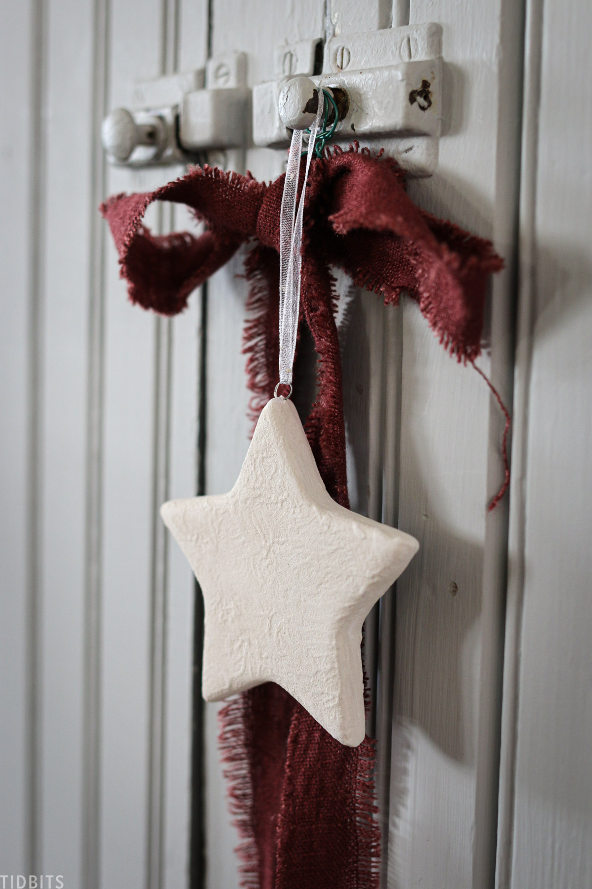 ceramic star hanging with red ribbon off a handle on a cabinet