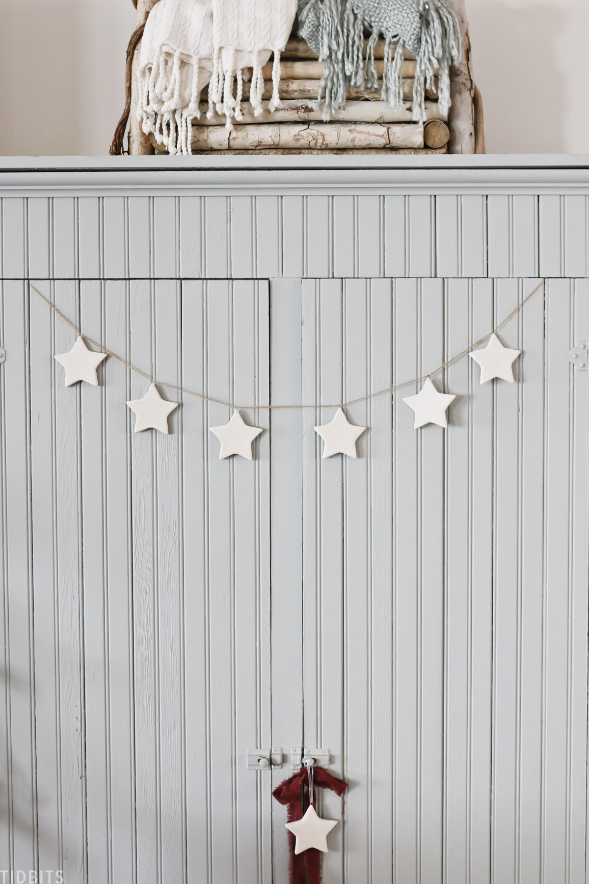 ceramic Christmas star ornaments hanging on cabinet in living room with other holiday decor