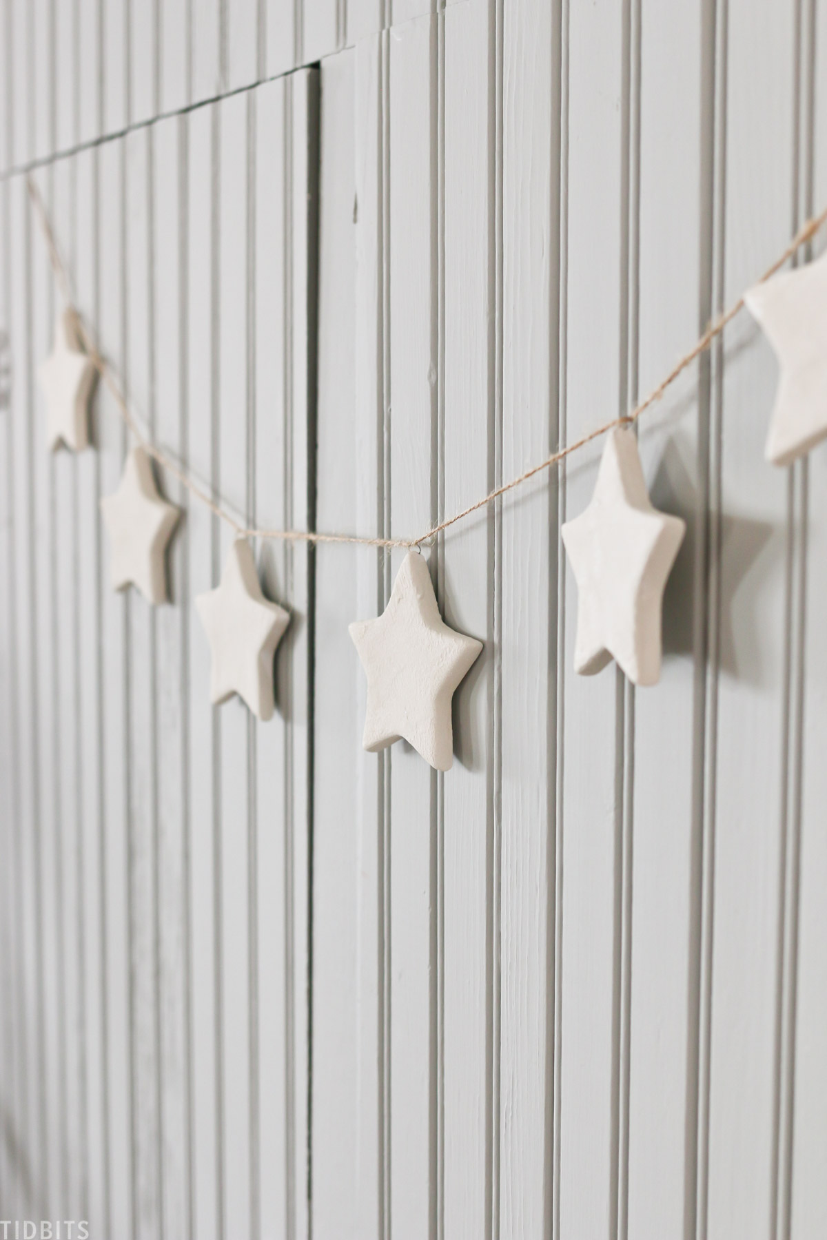 ceramic Christmas star ornaments hanging on furniture in living room with other holiday decor showing details on the stars