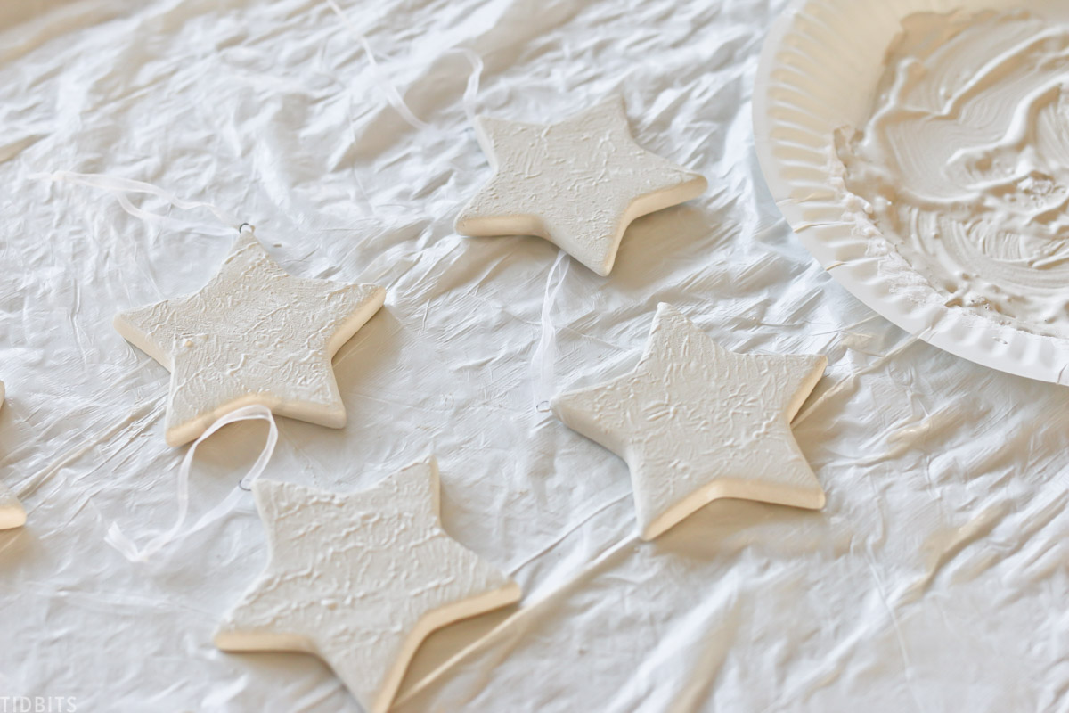 white ceramic stars laid out on sheet for painting