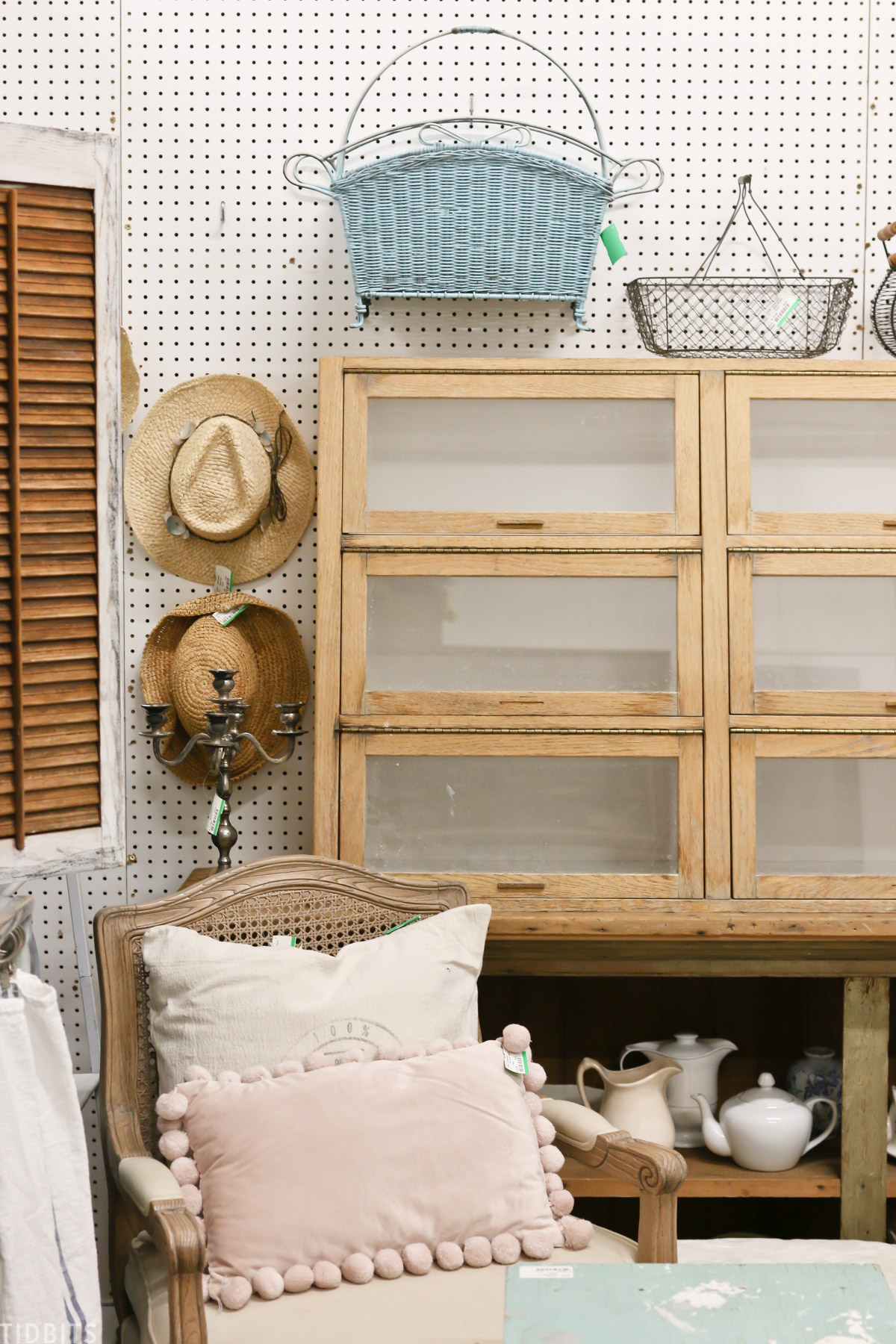 cabinets, a bookshelves, and an armchair placed in the corner of the antique booth