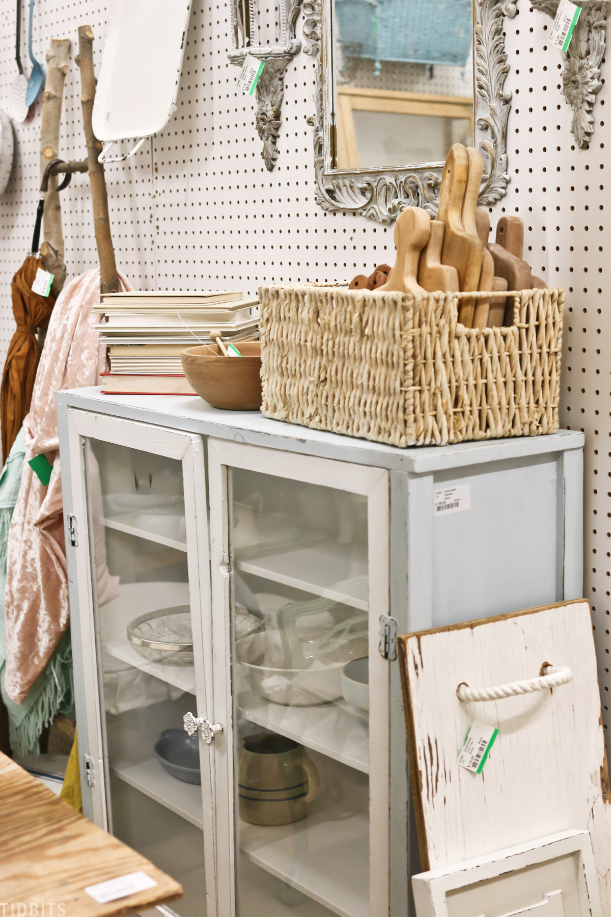 antique cabinet with glass doors with basket on top that has cutting boards in it