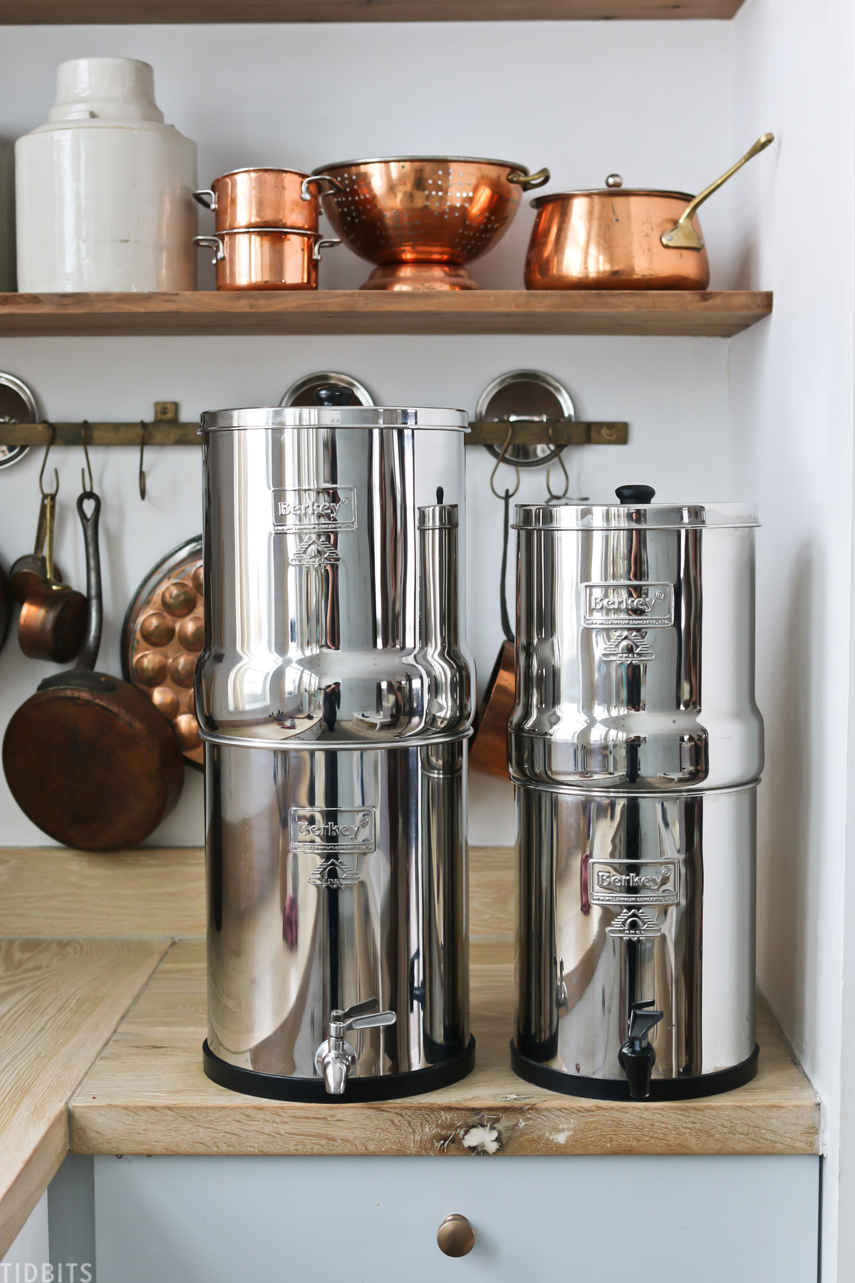 two different sizes of the Berkey Water Filter placed side by side on a kitchen countertop