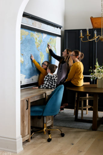 four kids looking at a world map in a converted room used for homeschooling