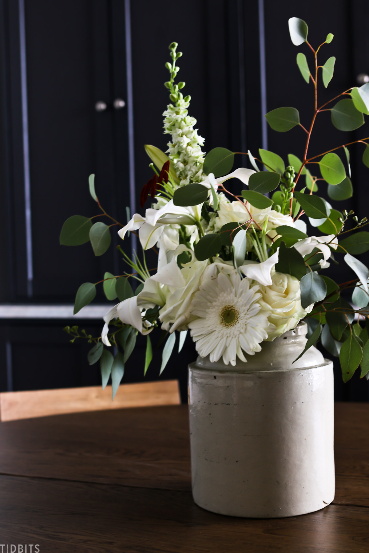 flowers placed in antique vase that's used as a centerpiece on a roundtable