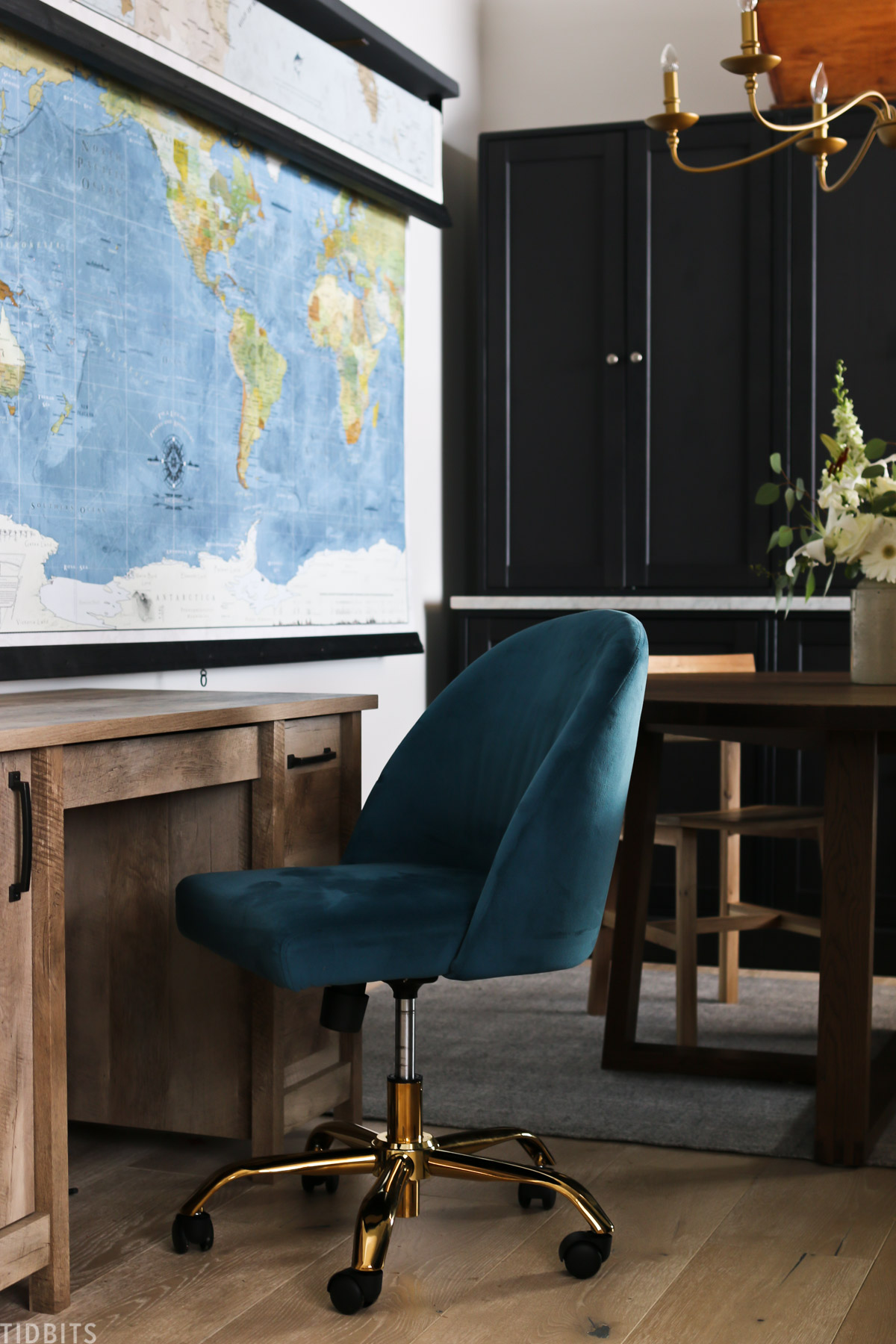 blue chair, a desk, and two pulldown maps in a homeschool room