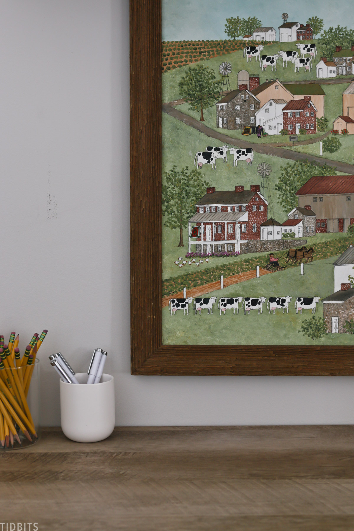 wall art depicting scene of farming communities with charming homes, roads, animals and people out enjoying the land