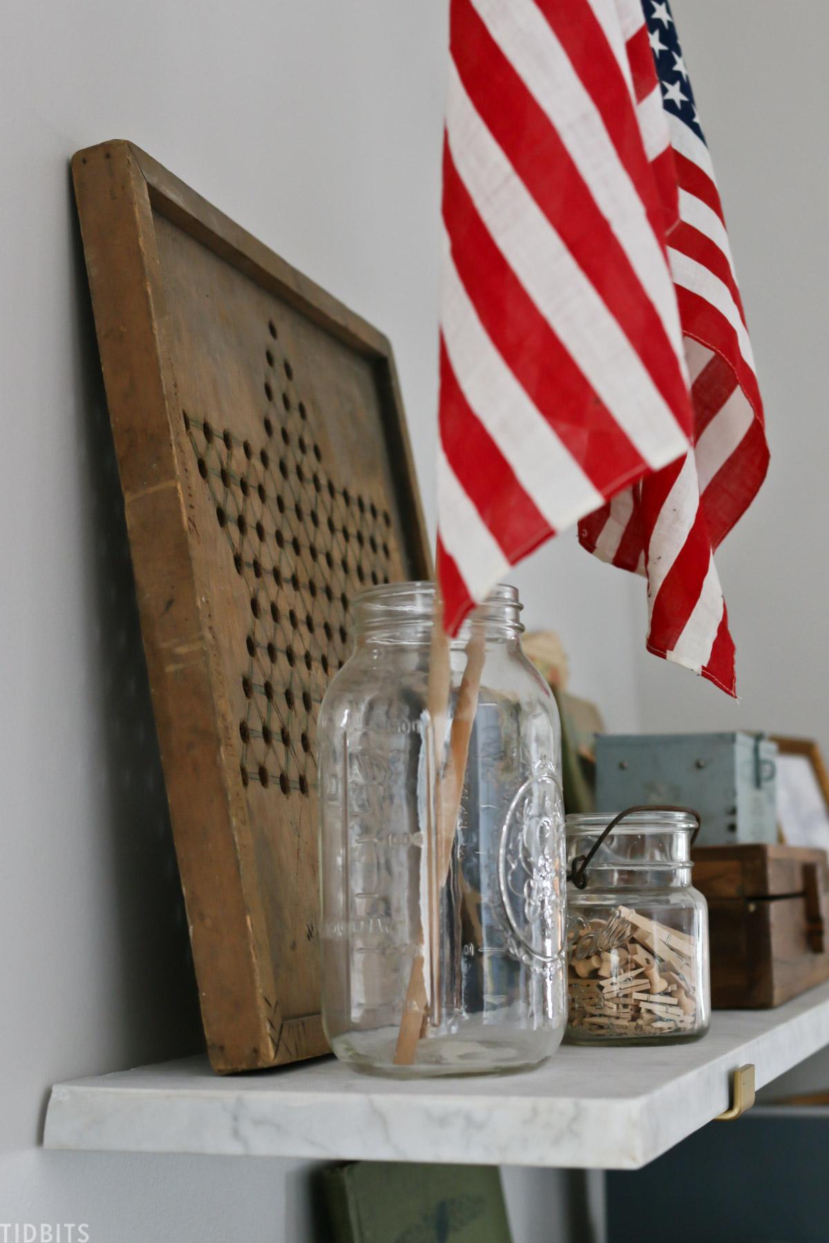 Mason jar holding a United States flag. The mason jar is on a floating shelf.
