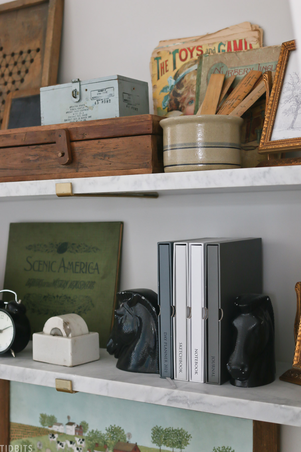 planner, sketchbook, notebook, and journal placed on a bookshelf with decor items
