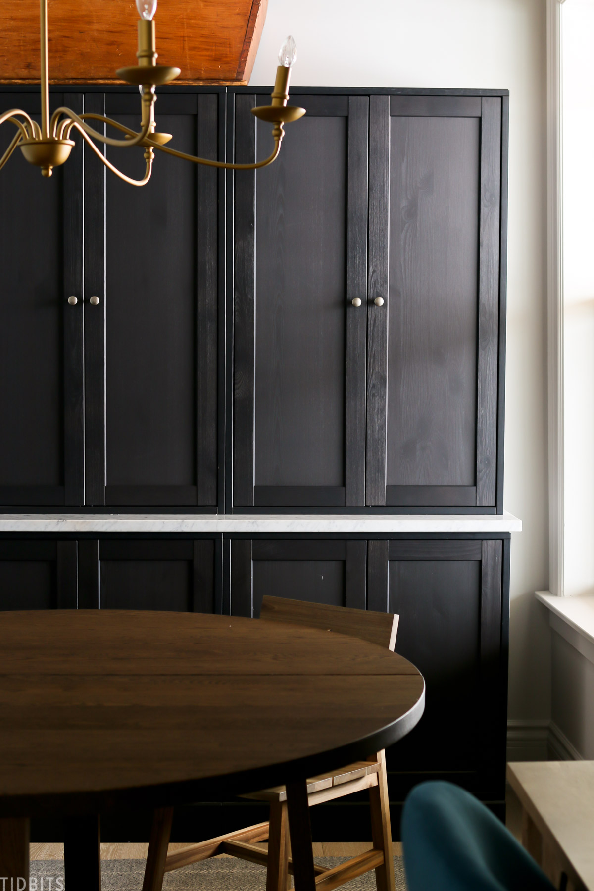 round table and chair in front of black Havsta cabinets