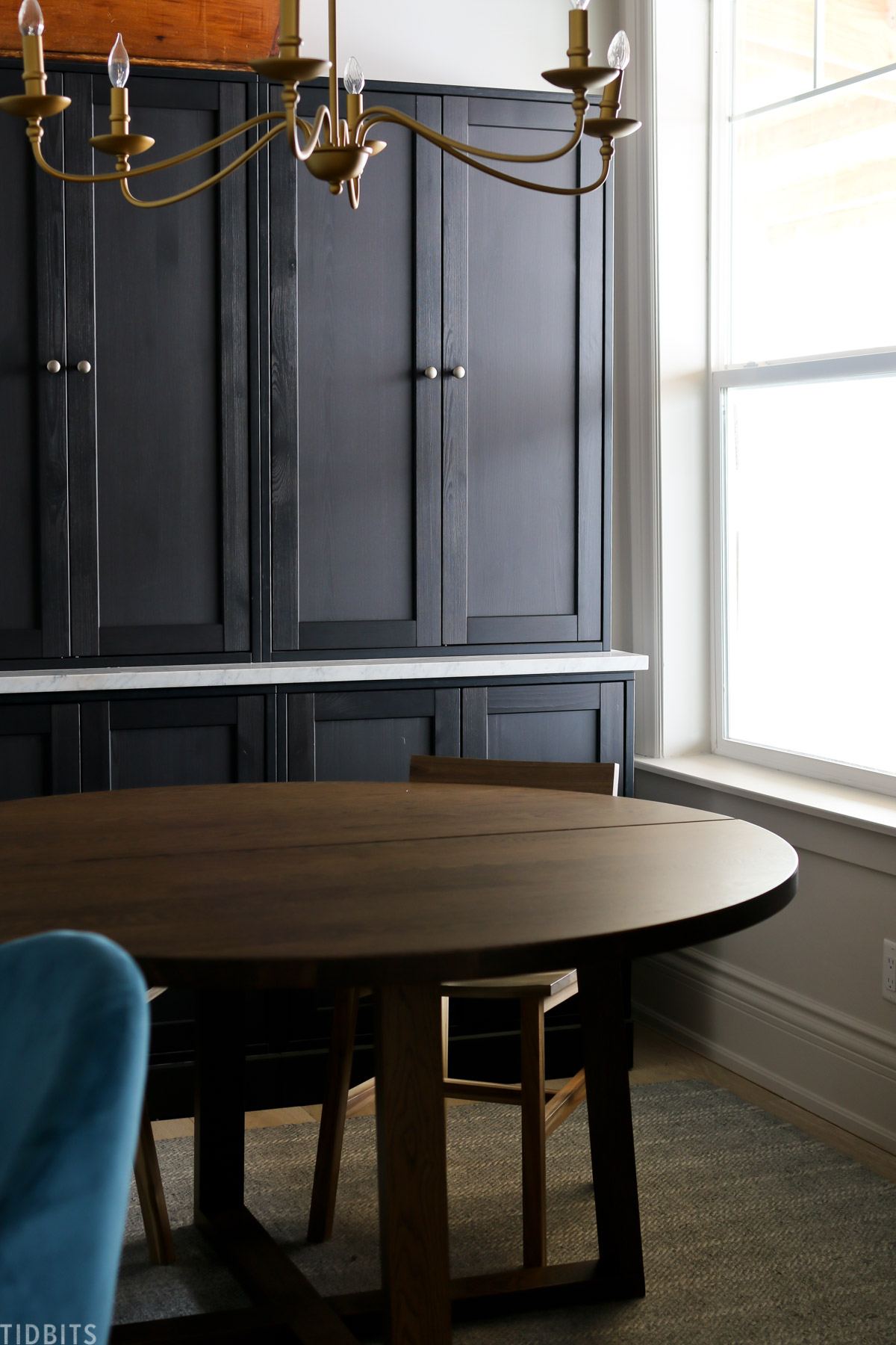 round table and chairs in front of black Havsta cabinets