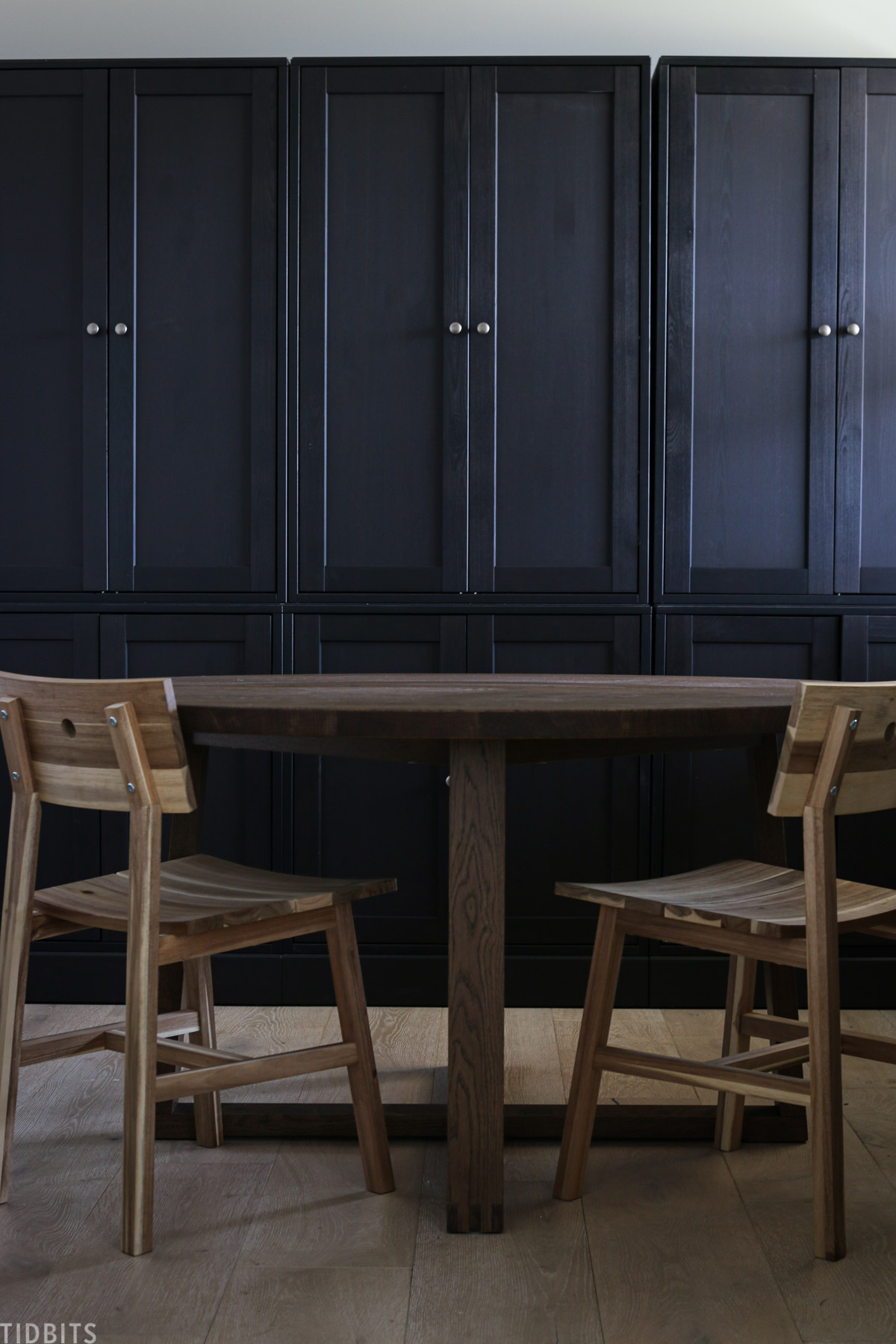round table and two chairs in front of black Havsta cabinets made by IKEA