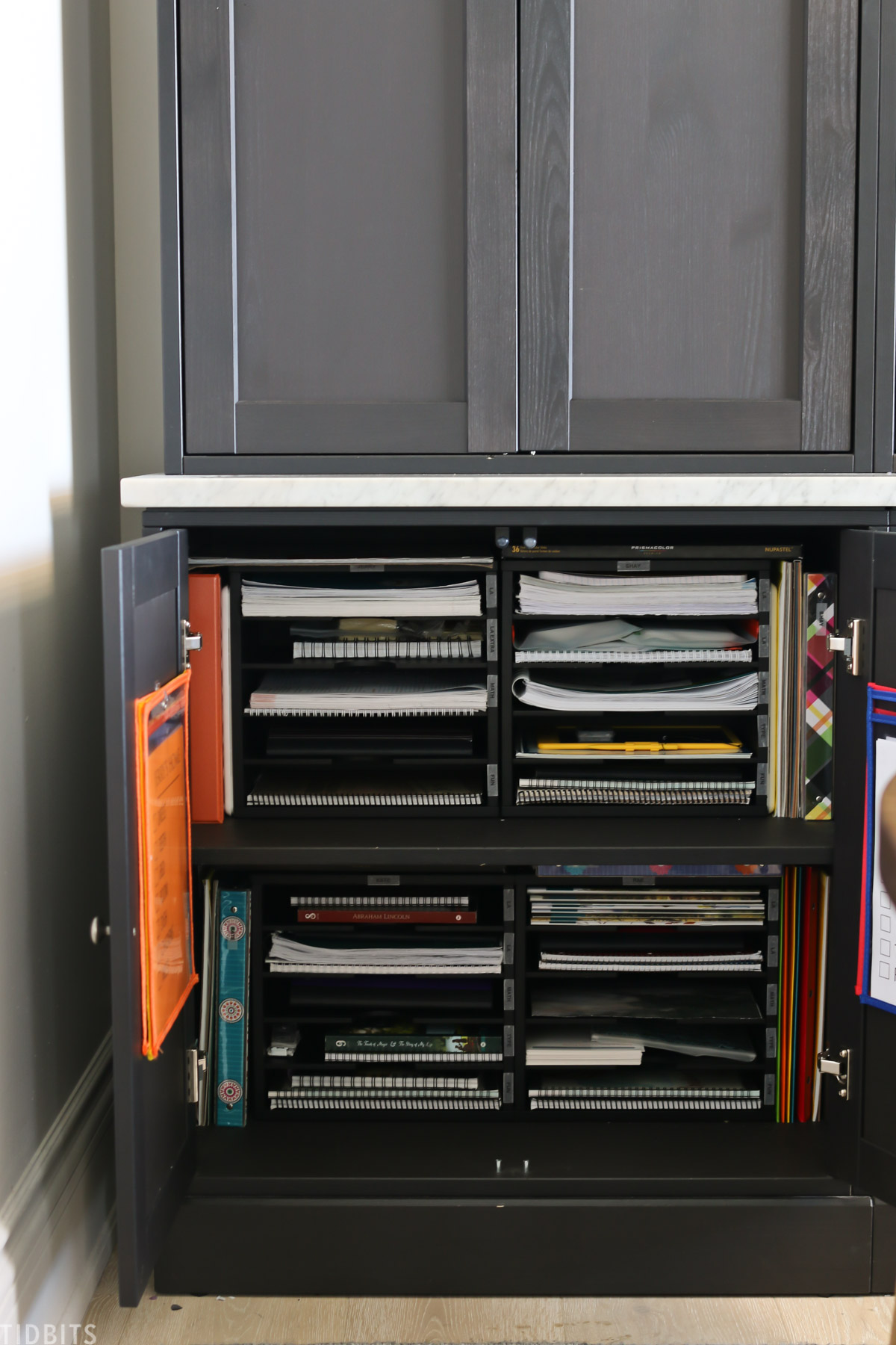 lower storage cabinets showing file organizers filled with paper, notebooks, and binders