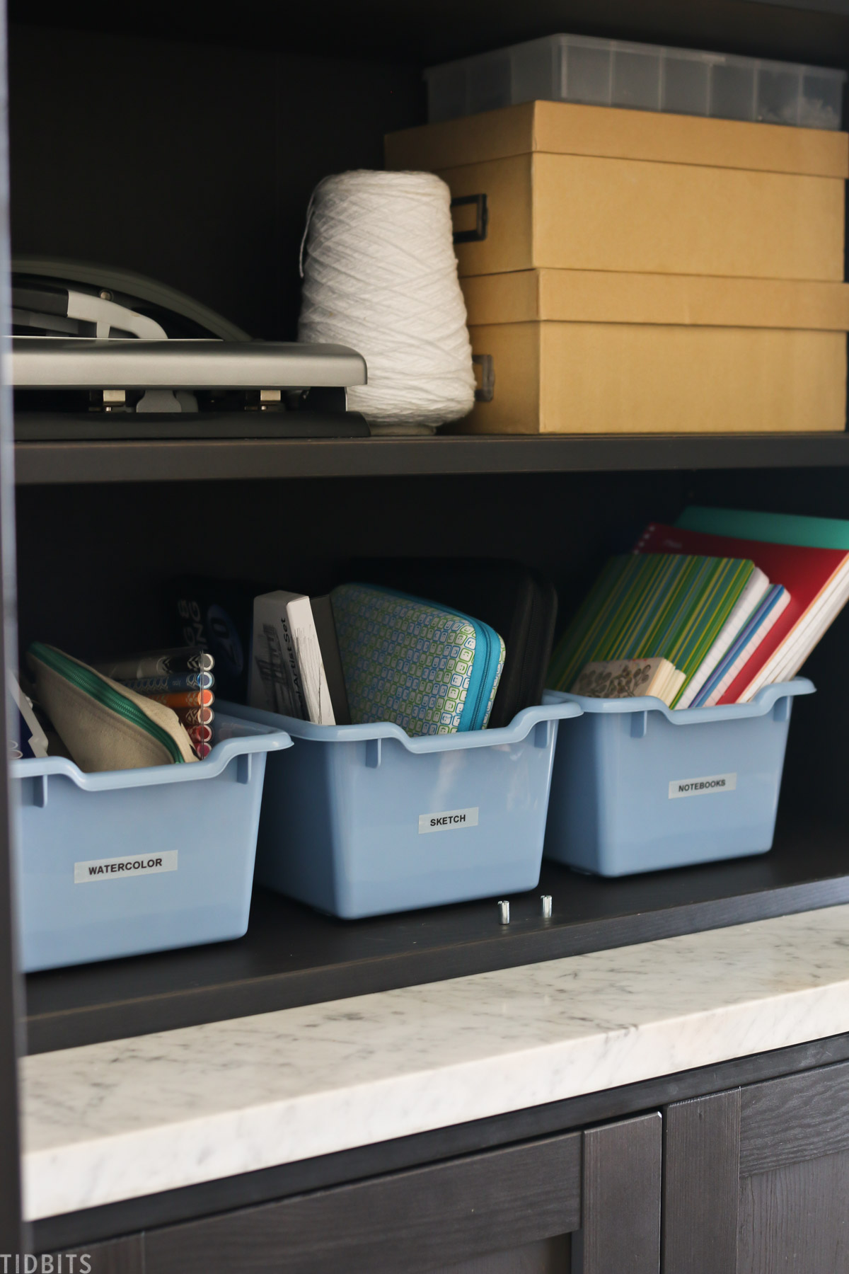 blue storage containers are labeled with homeschool supplies