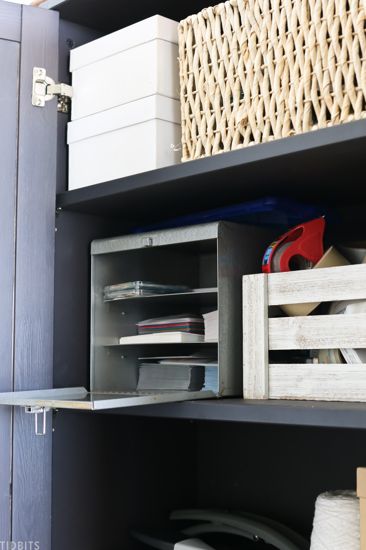storage containers within a storage cabinet that contain school and office supplies