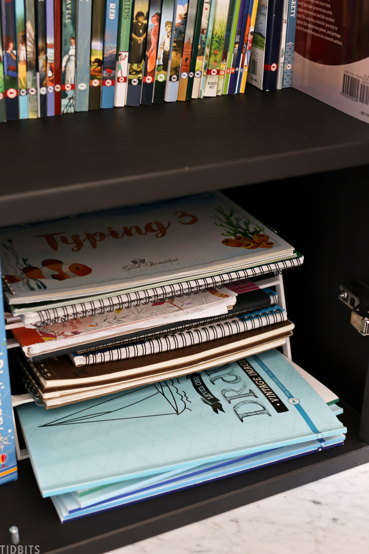 lower storage cabinet shows workbooks for typing and drawing are stored in a stacked file organizer