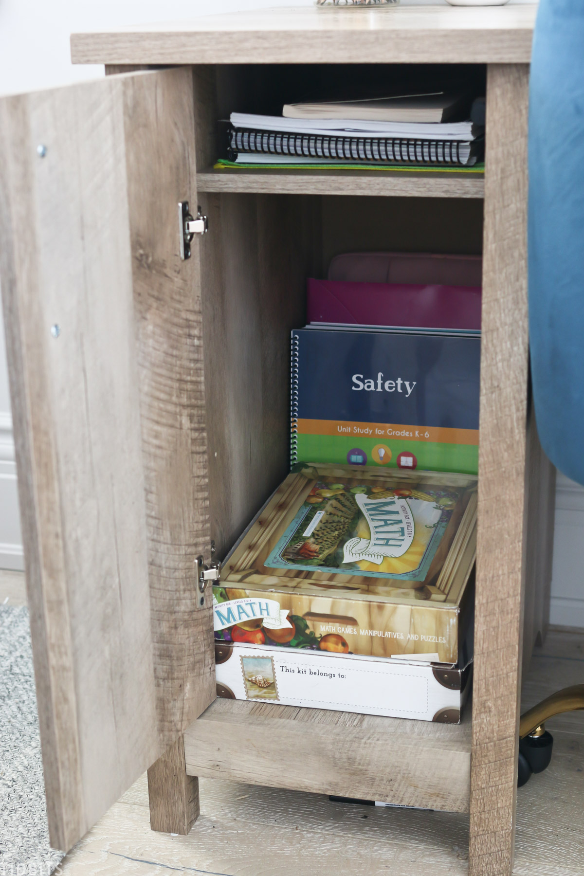desk cupboard is opened to show the school workbooks that are stored inside
