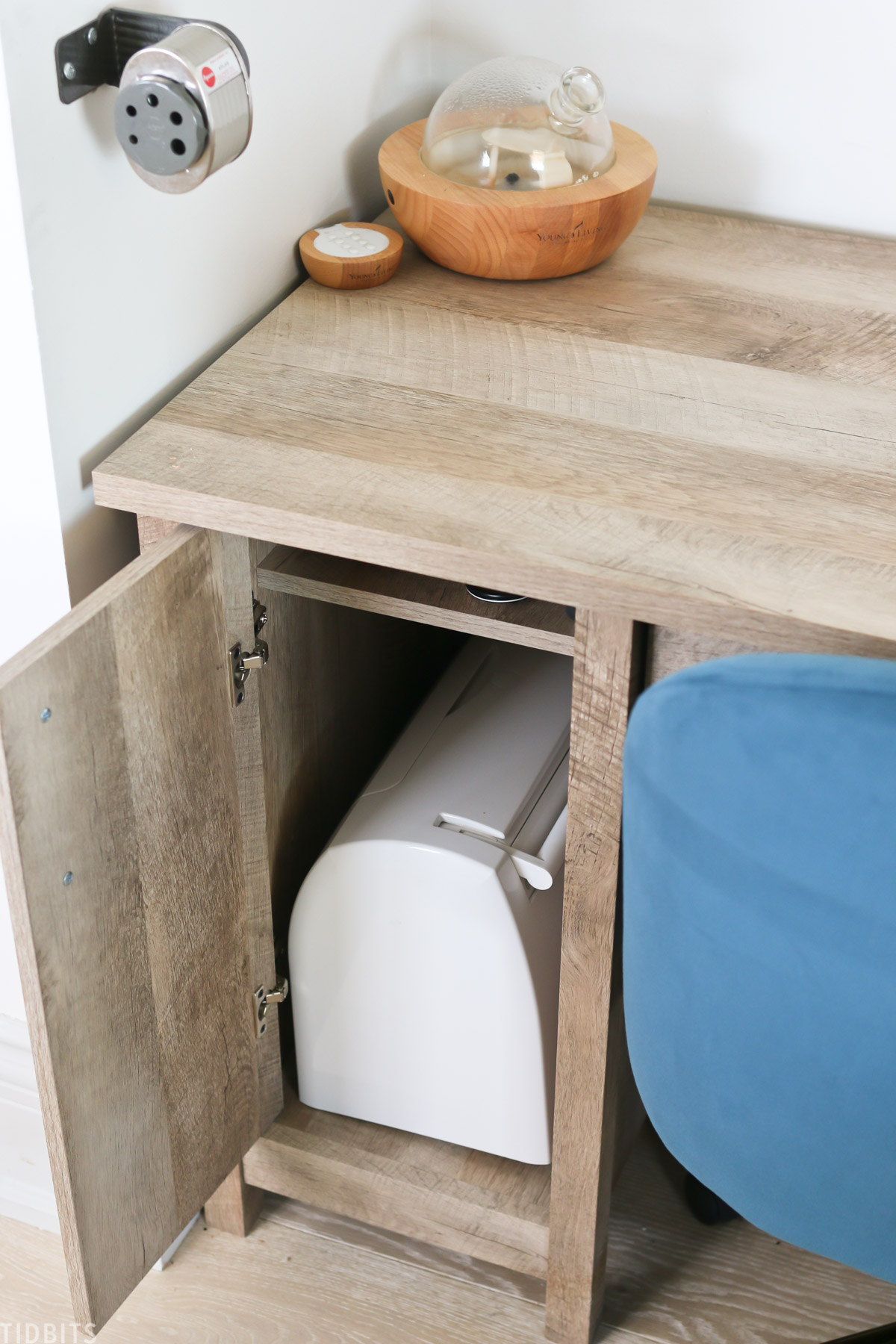 desk cupboard is opened to show that a sewing machine is being stored inside