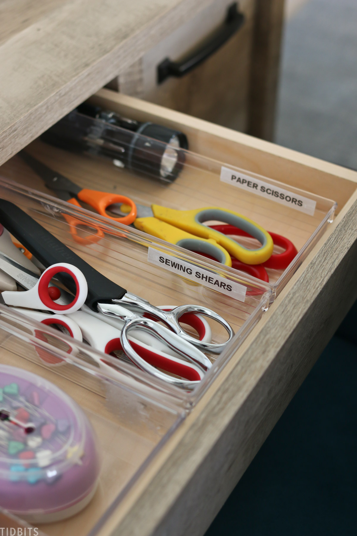 desk drawer is opened to show three containers organizing paper scissors, sewing shears, and sewing needles