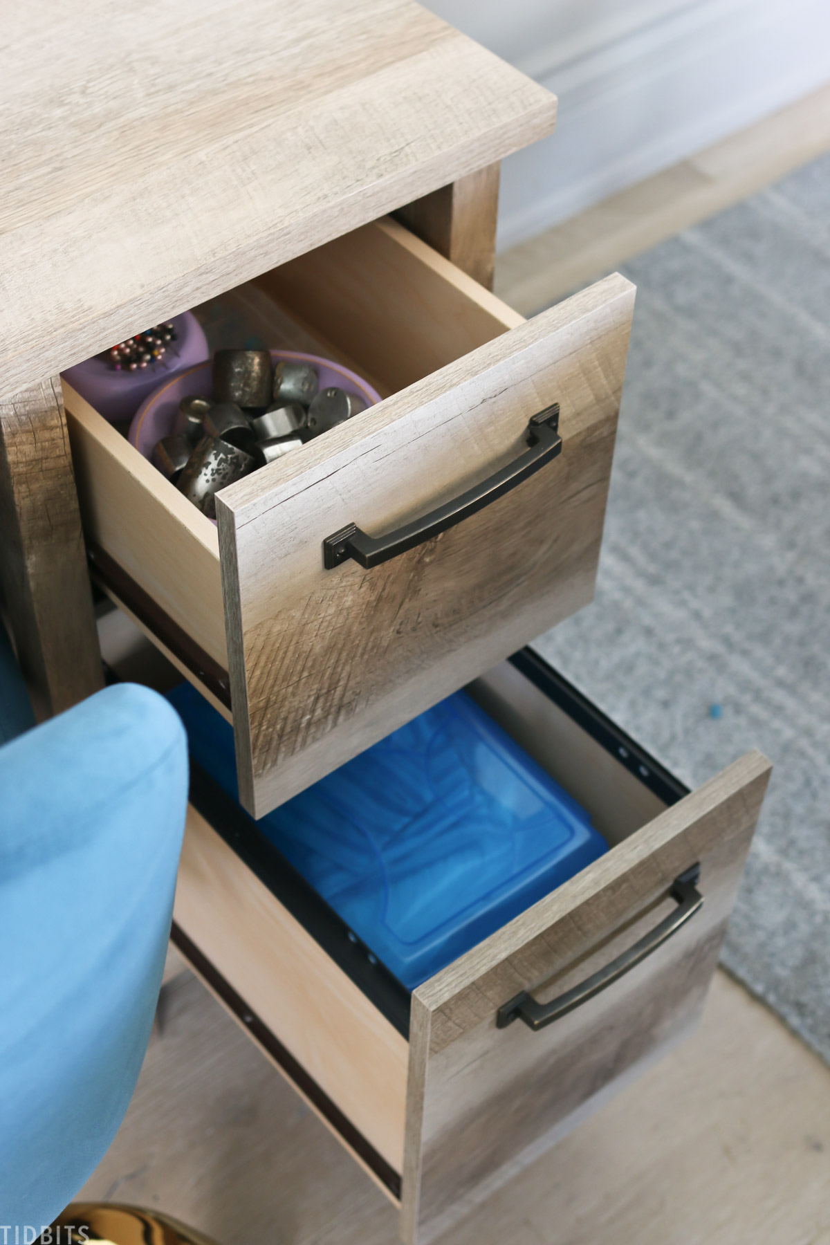 two desk drawers are opened to reveal the sewing supplies stored inside
