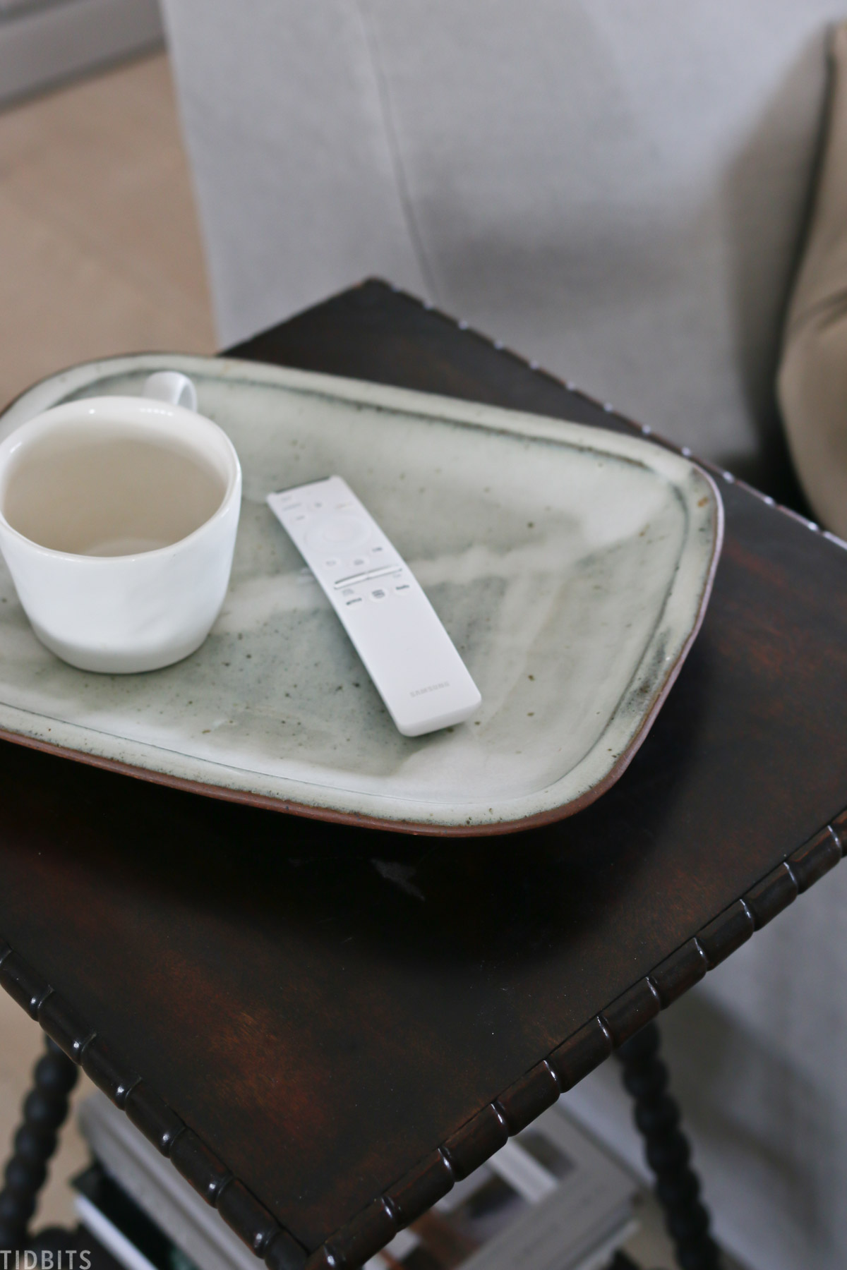 ceramic tray on a side table with a remote and mug on top of it