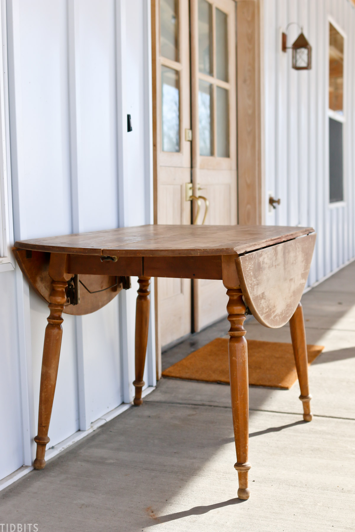 antique drop leaf table sitting on front porch near front door