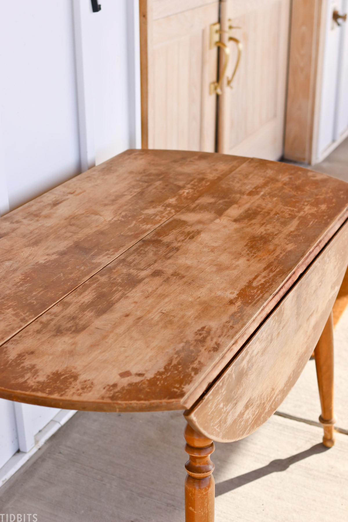 top view of antique drop leaf table sitting on front porch near front door