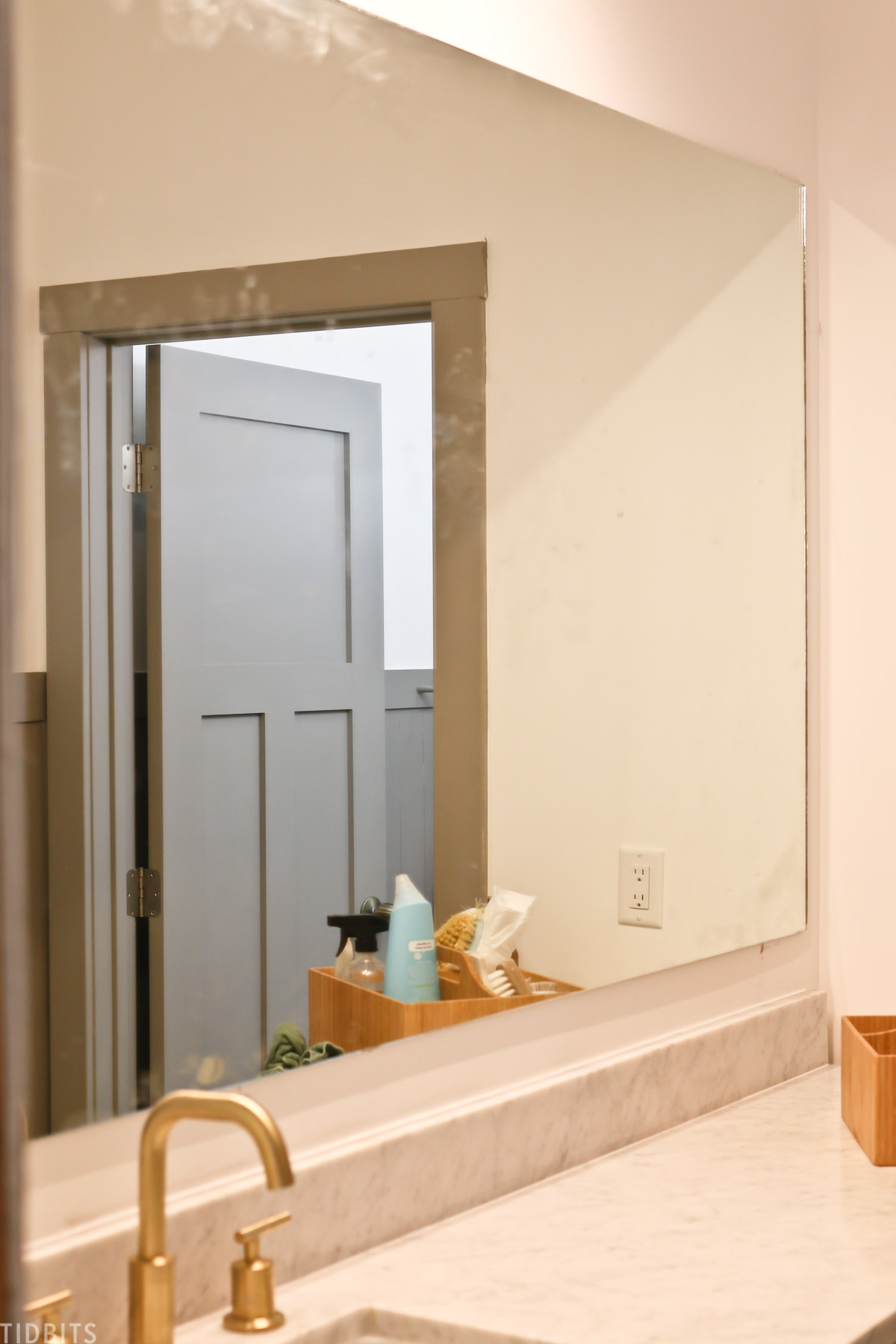 large mirror attached to wall above bathroom vanity with construction adhesive