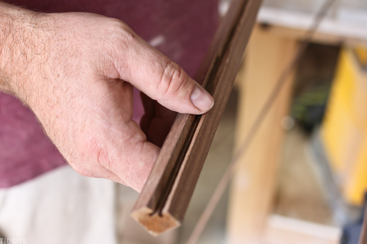 man holding up wood piece that shows a one corner is miltered at a 45 degree angle