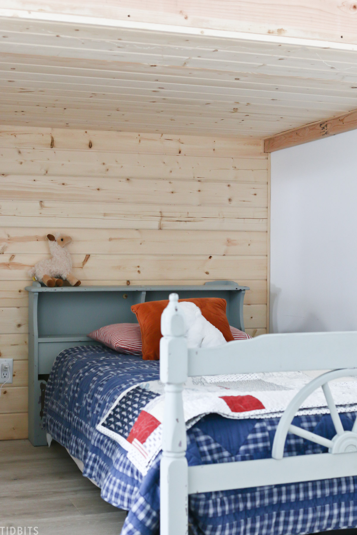 shiplap planks installed on the wall behind a bed