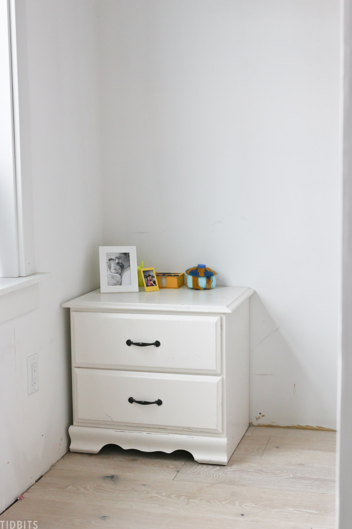 side table placed in corner of kids' bedroom, showing that flooring and wall are in progress during remodel