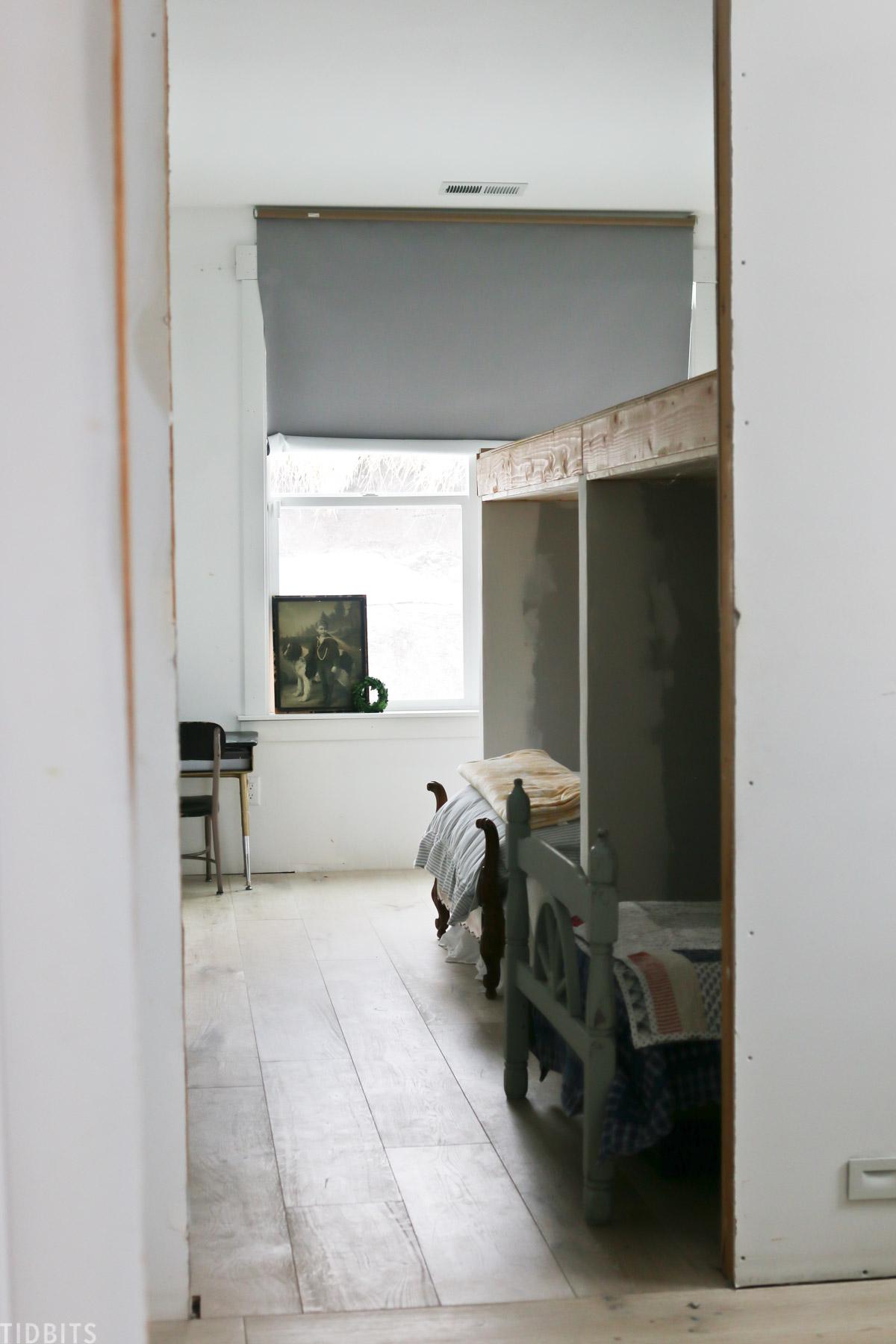peak inside a kids' bedroom in a pole barn home, revealing two beds underneath a play loft