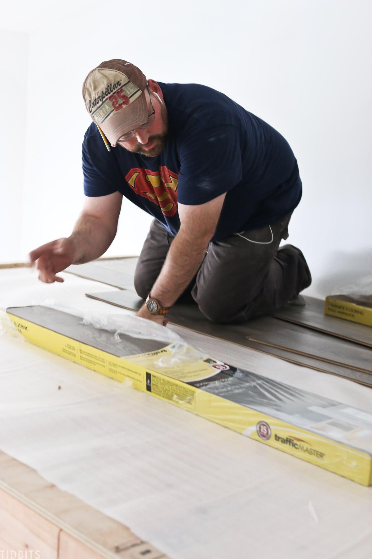husband installing inexpensive wood flooring into loft area in kids bedroom