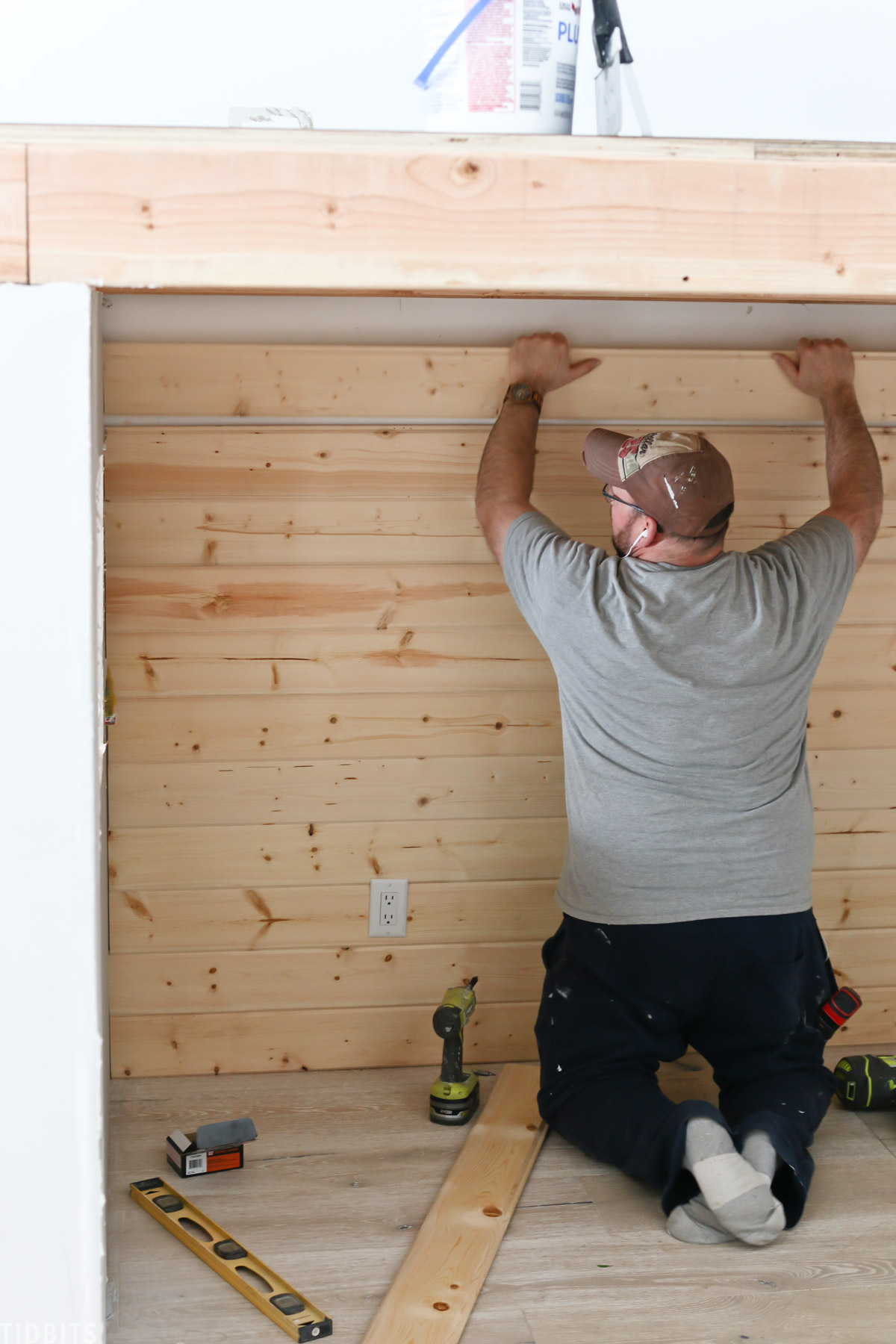 husband installing shiplap planks into the bedroom wall below the play loft