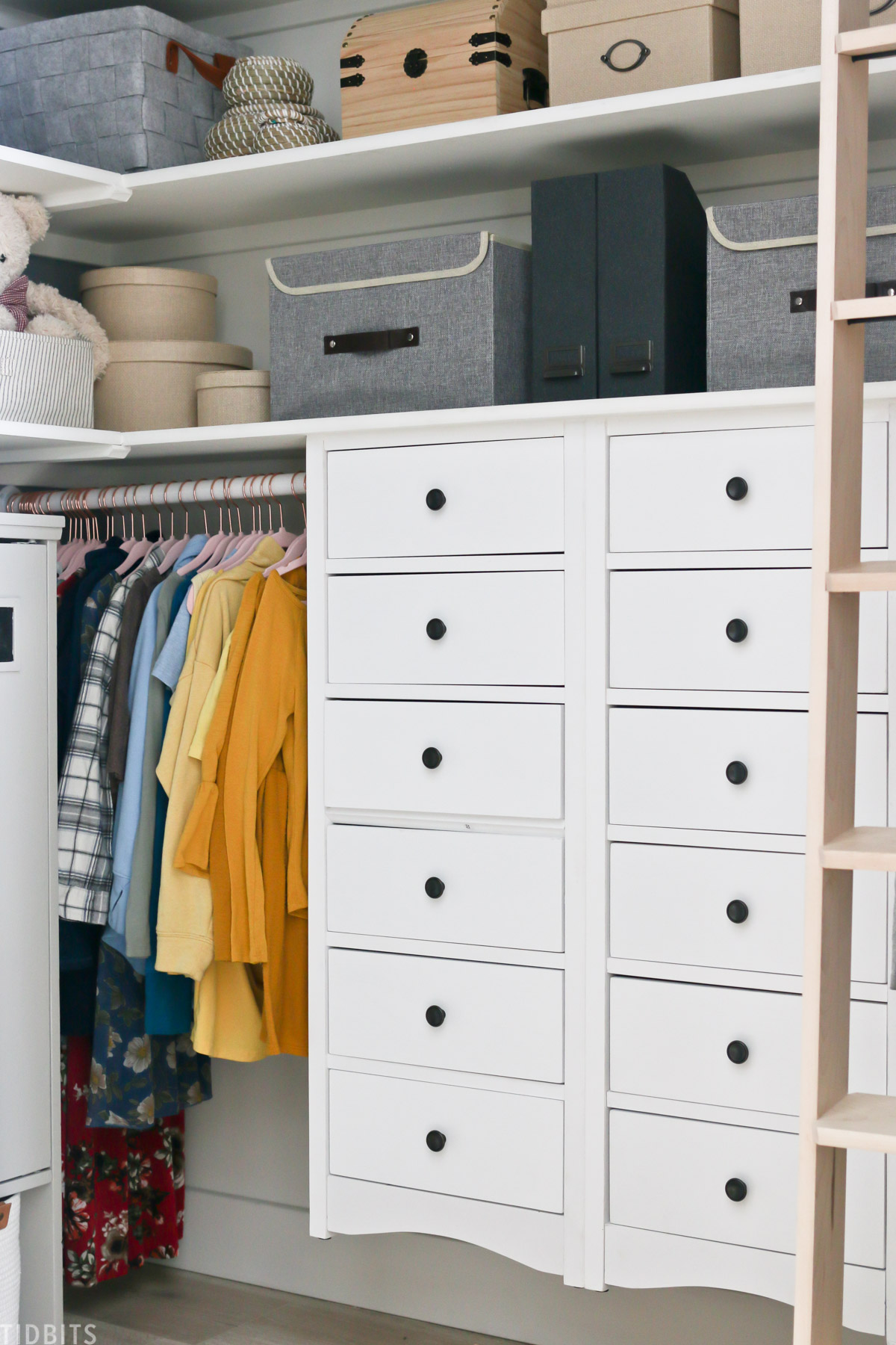 two tall white dressers in a walk in closet with clothes hanging next to them