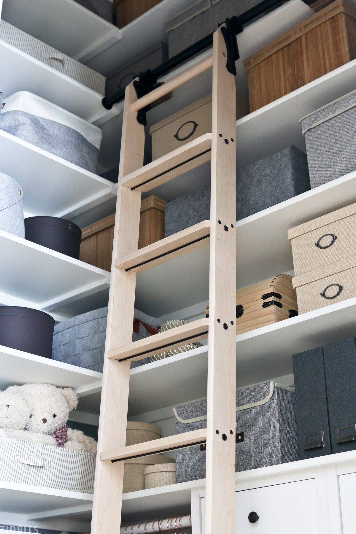 ladder inside of a kids closet with storage bins placed on built in shelves