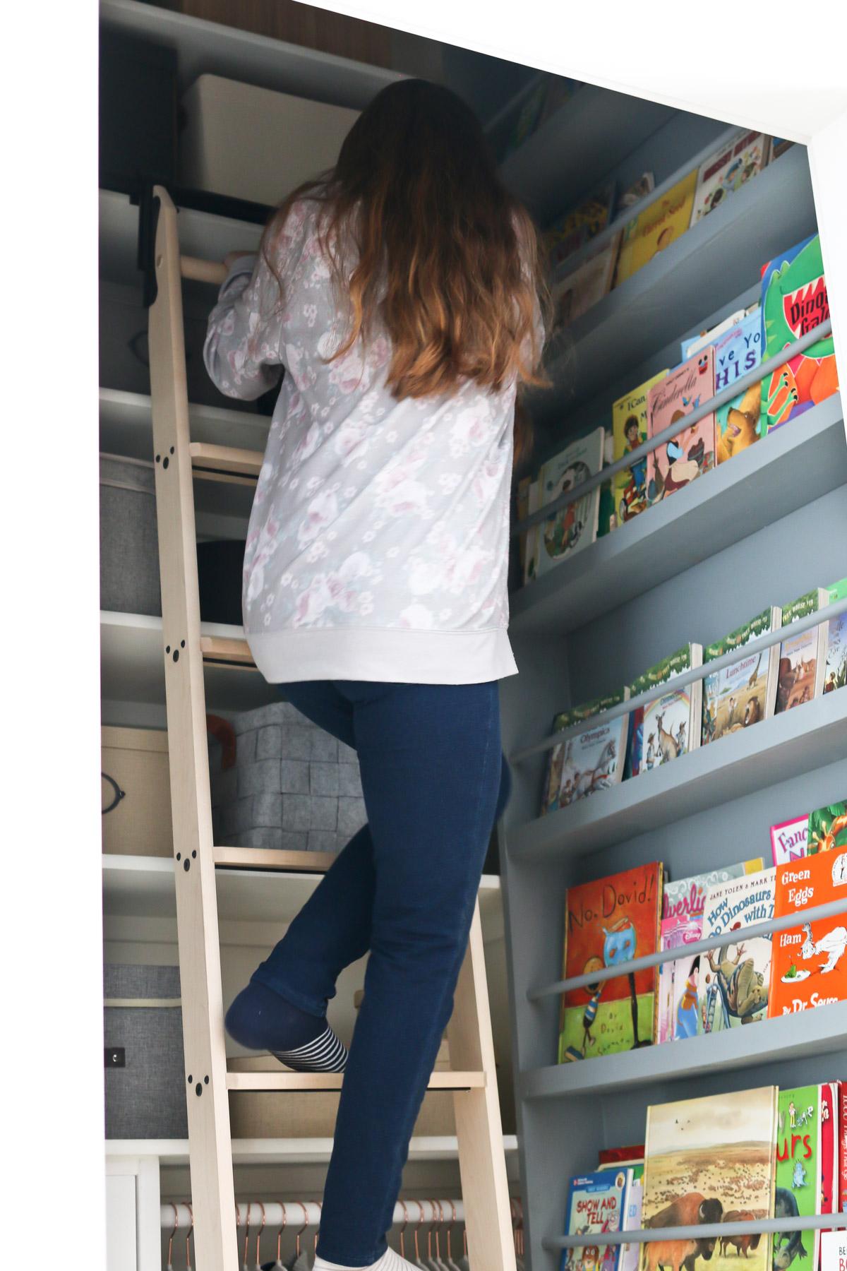 young girl climbing a ladder to reach a book