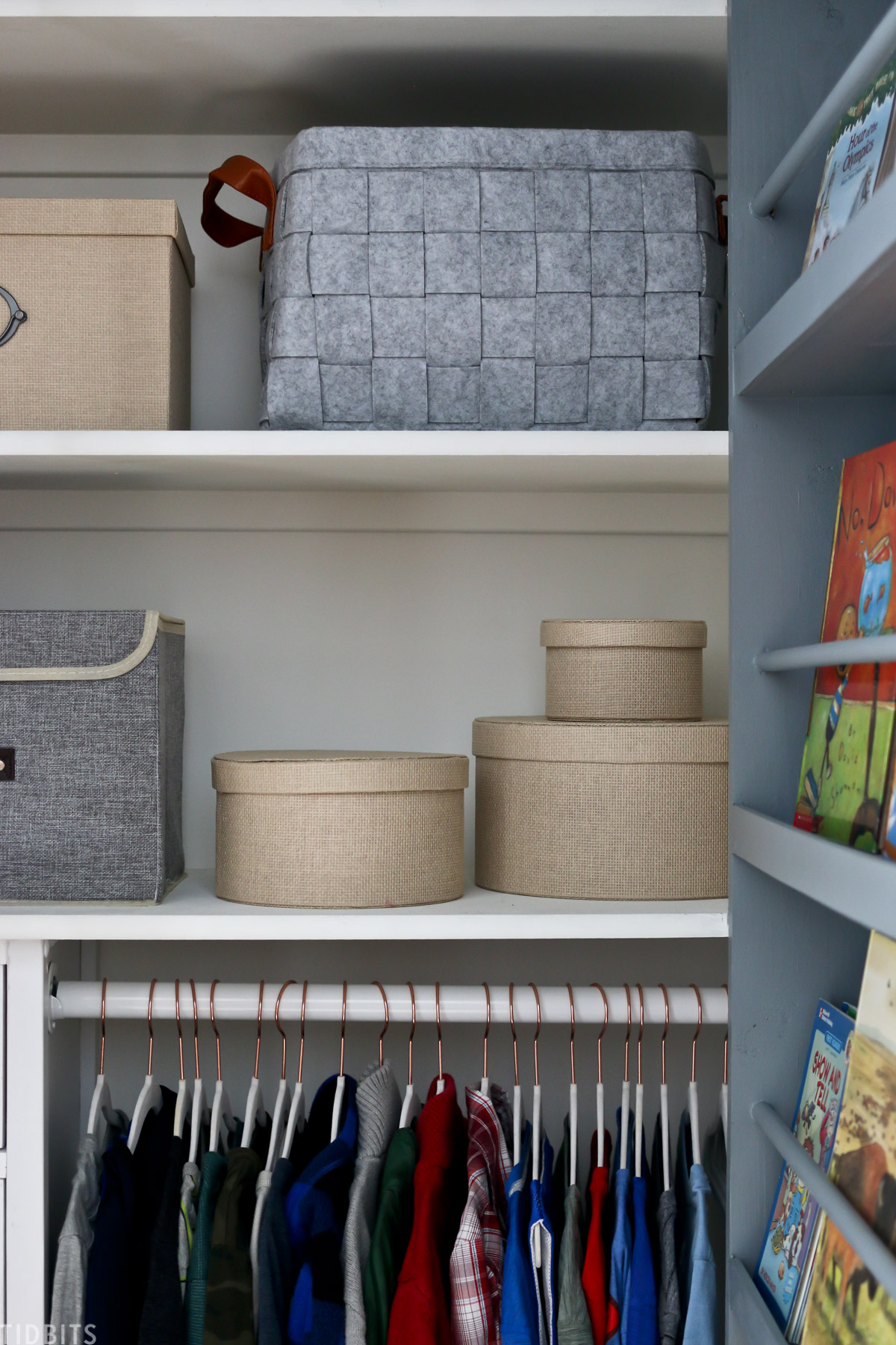 storage baskets and containers on two shelves within a walk in kids closet