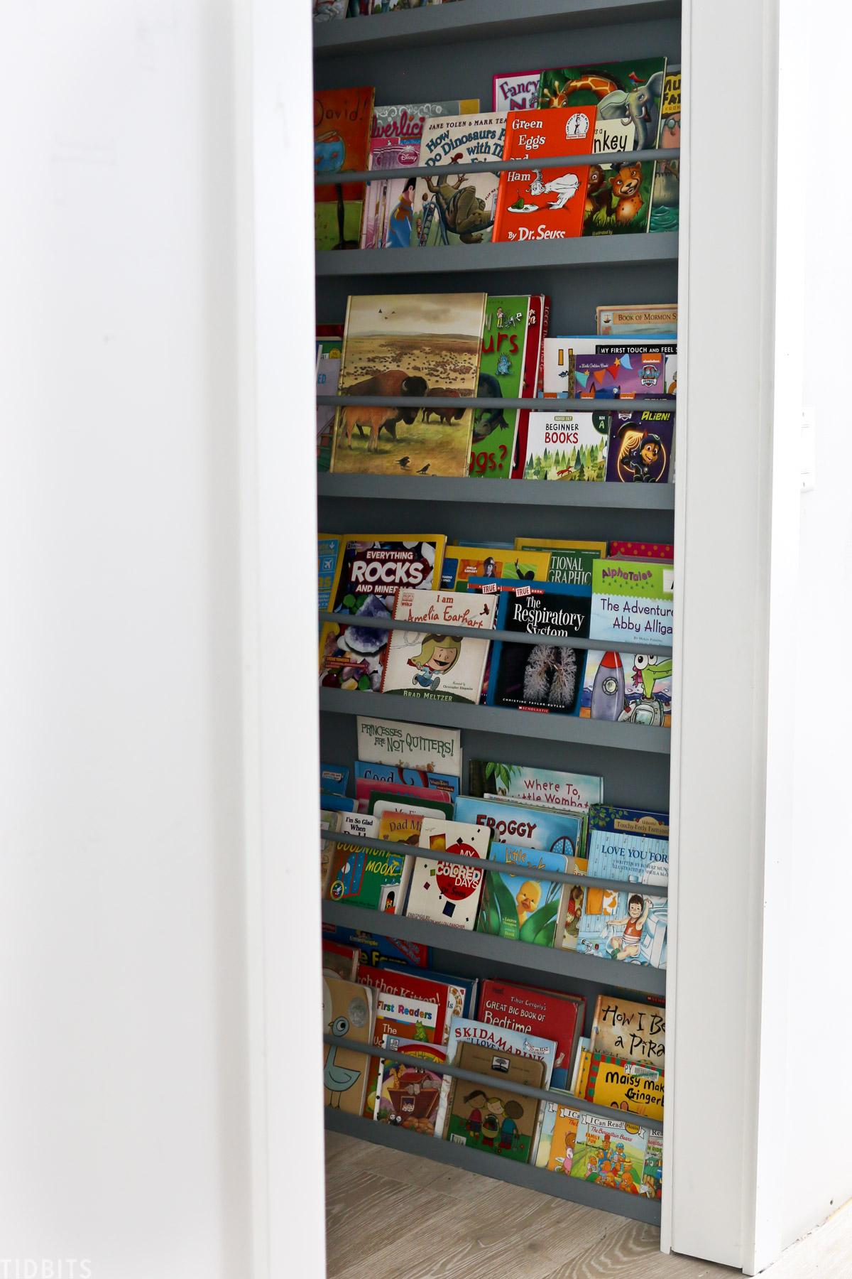 dozens of kids books stored on shelves inside of a walk in closet