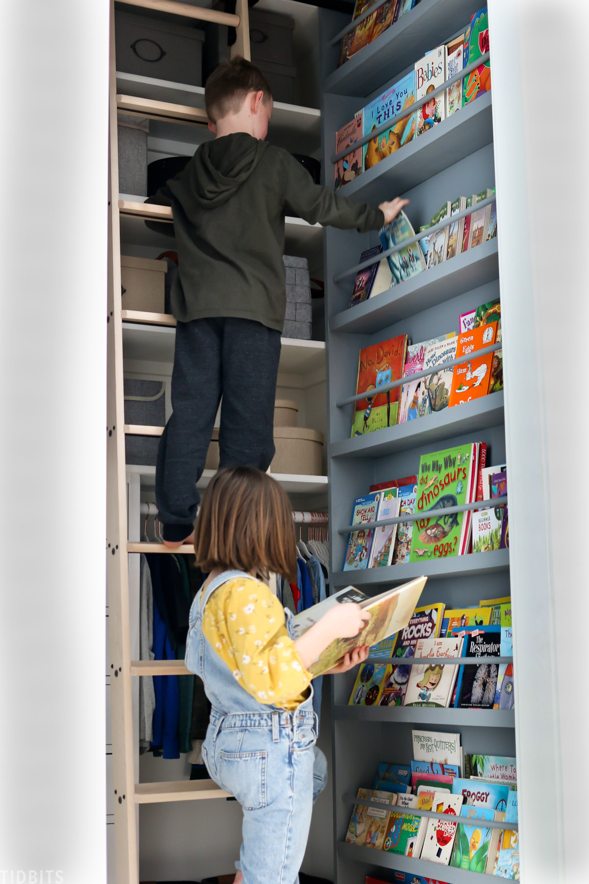young boy standing on ladder and a little girl standing nearby holding a book