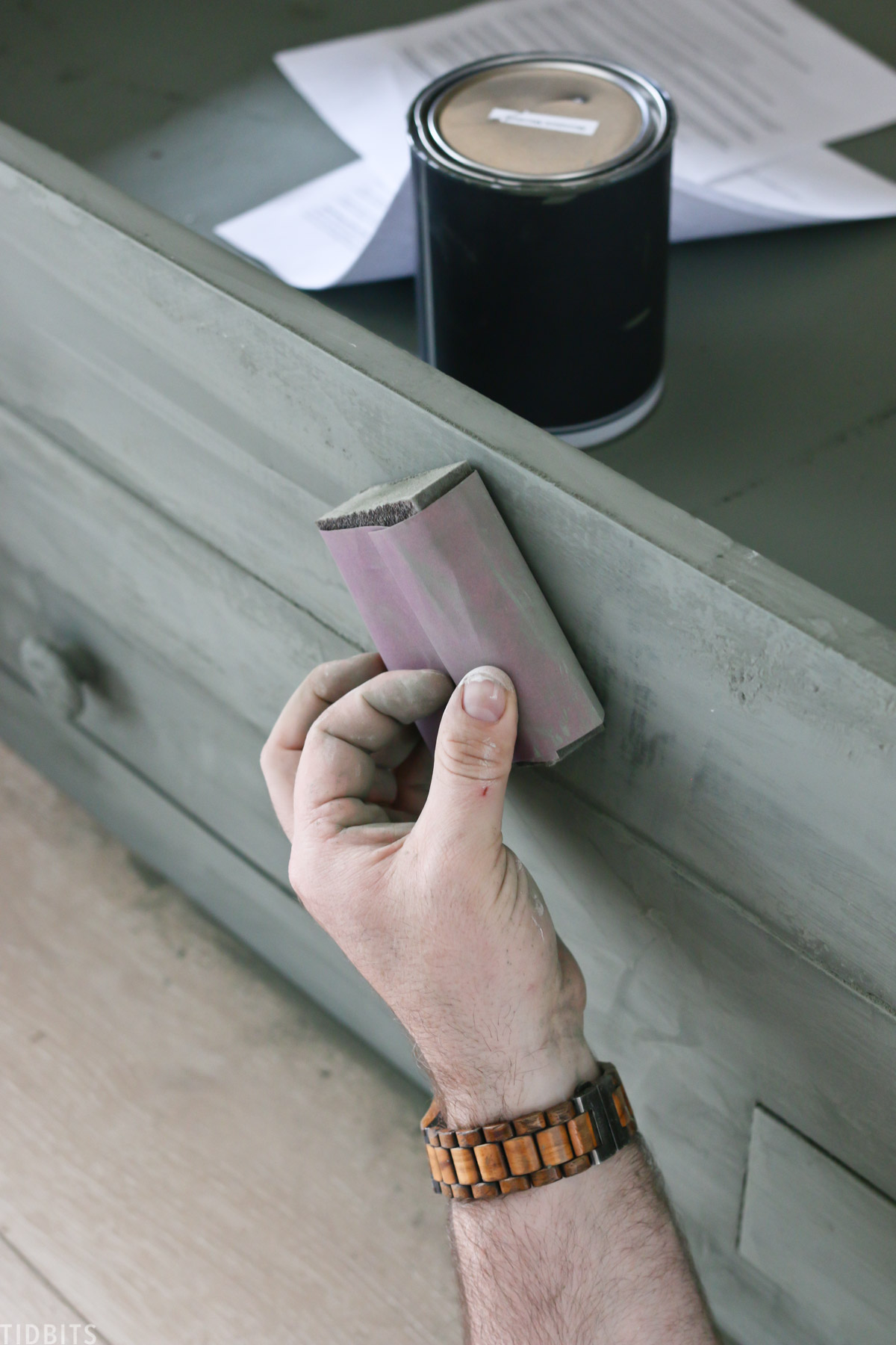 hand is sanding down recently painted bed frame