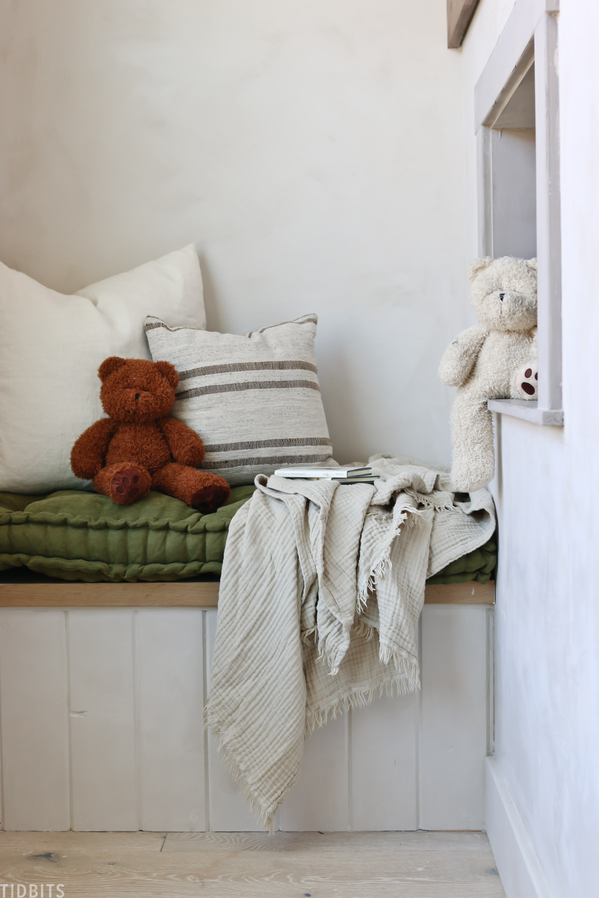 blanket hutch that has a teddy bear, pillows, and blanket on top of a bench cushion
