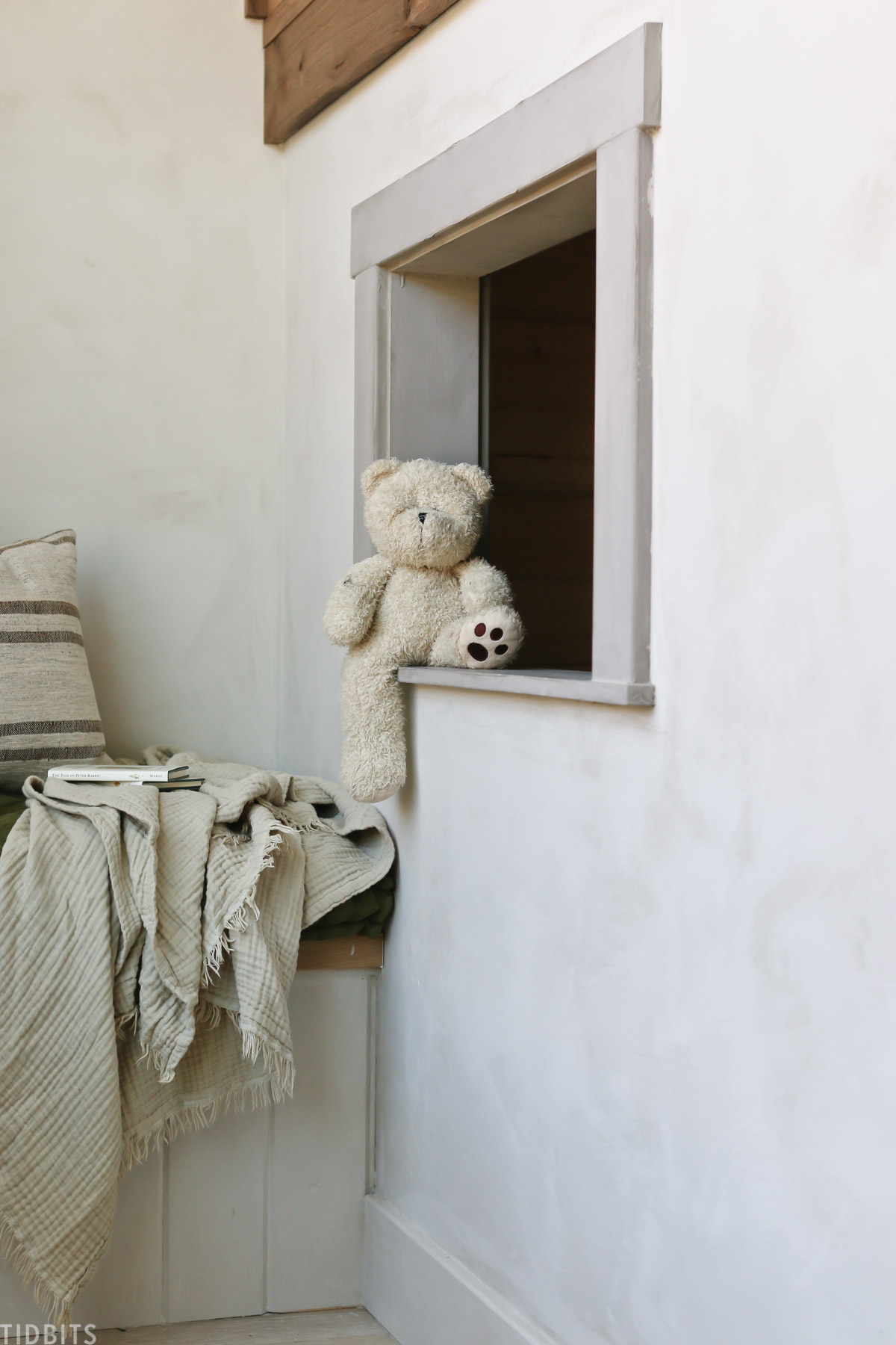 teddy bear placed on cut out square in bedroom, which resembles an open window