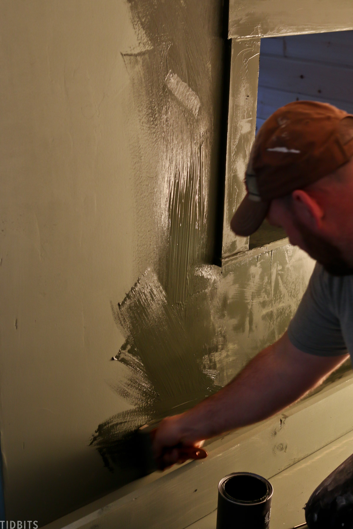 man is painting part of a wall inside of a kids' bedroom